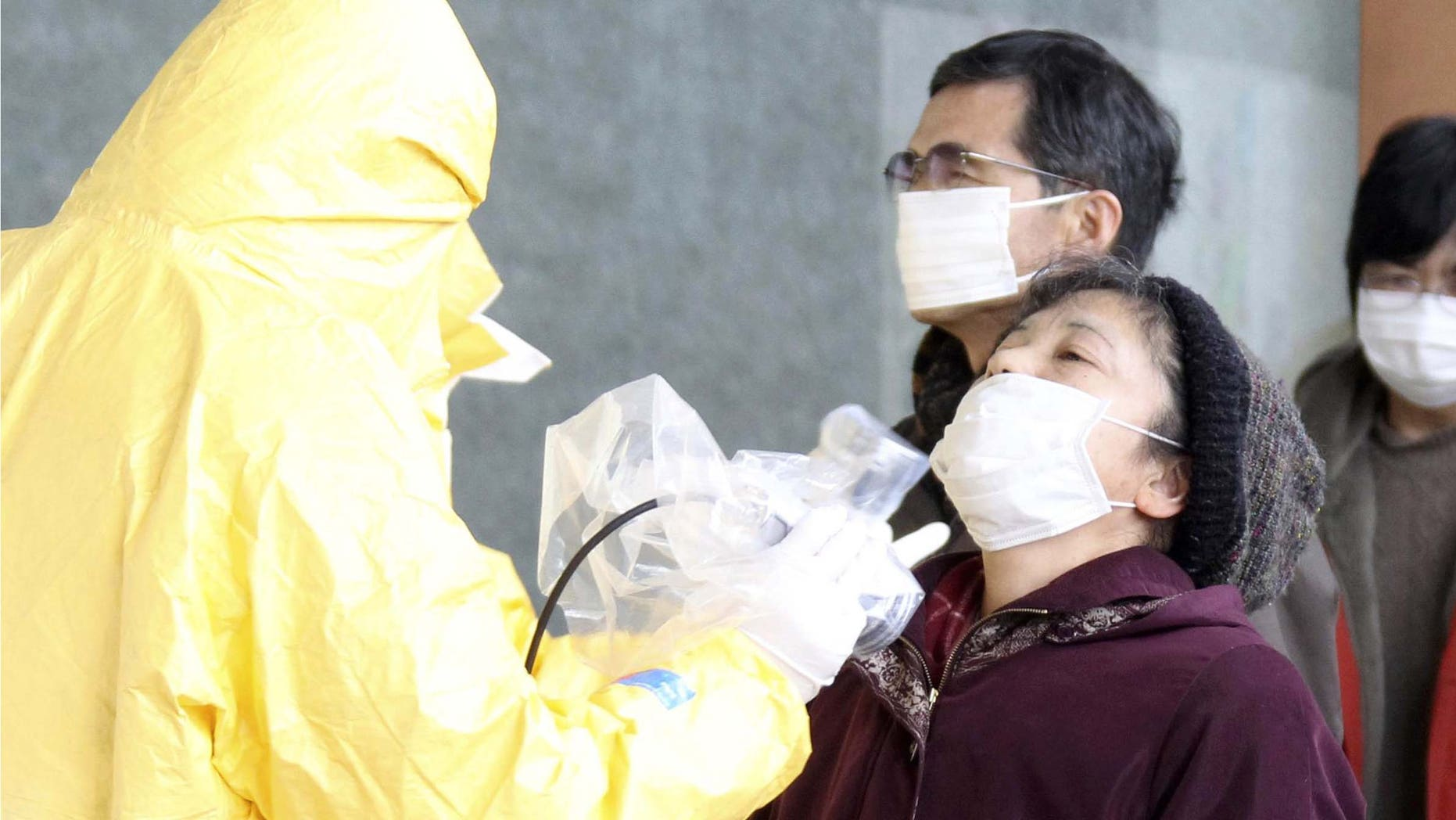 A woman is tested for radiation exposure in Nihonmatsu, northern Japan Wednesday, March 16, 2011 after Friday's massive earthquake and tsunami. (AP Photo/Yomiuri Shimbun, Koichi Nakamura) JAPAN OUT, MANDATORY CREDIT