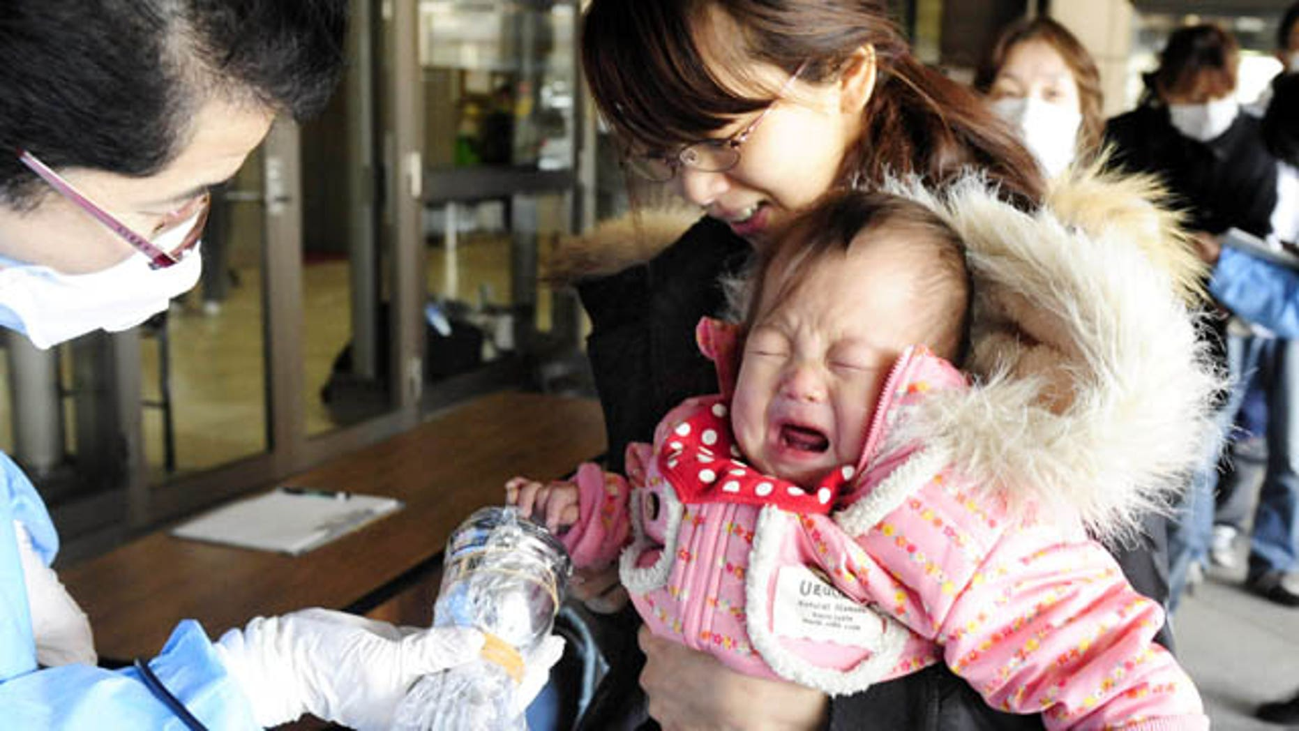 March 17: A baby cries as she is helped by her mother to be screened for radiation exposure before entering an evacuation center in Fukushima, northern Japan. (AP/Kyodo News)