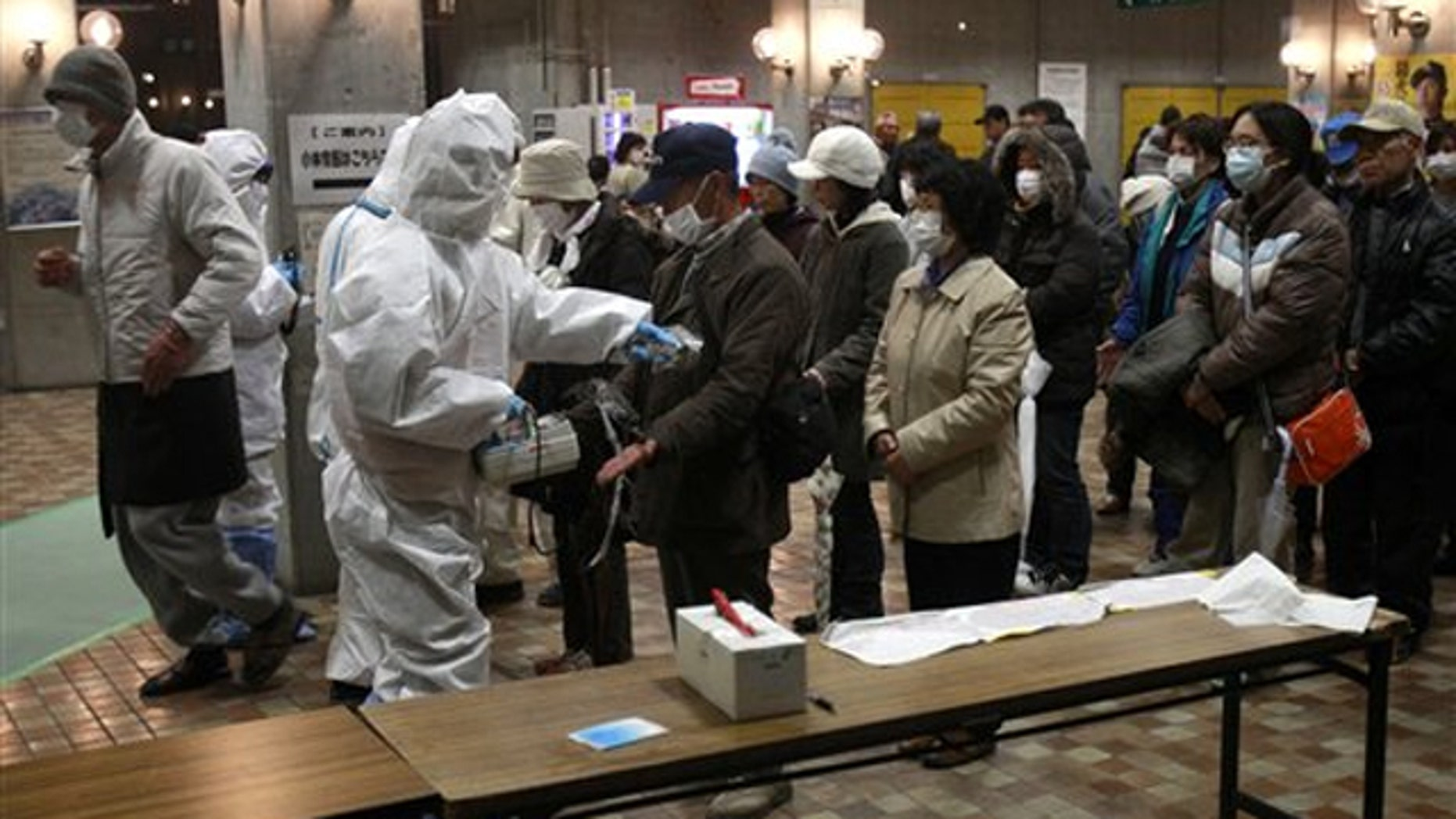 Evacuees are screened for radiation exposure at a testing center March 15 in Japan's Koriyama city.