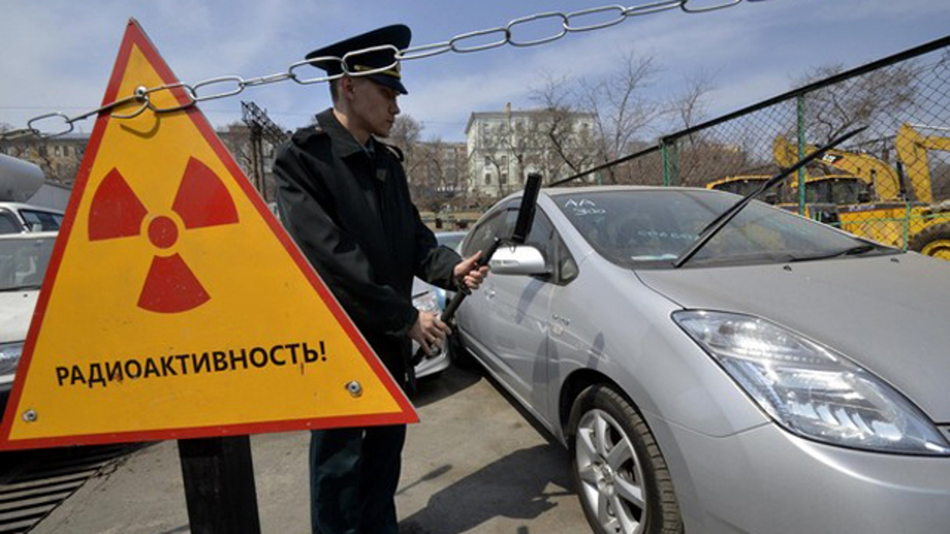 """A customs officer measures the radiation level of an automobile delivered from Japan, in Russia's far eastern city of Vladivostok April 14, 2011. About 300 cars and other vehicles are delivered from neighbouring Japan to the port. Radioactive background has been revealed in 49 vehicles lately. These machines will be kept in the port until the Russian Federal Service on Customers' Rights makes a decision on their fate, Russian customs officers said. The sign reads """"Radioactivity""""."""