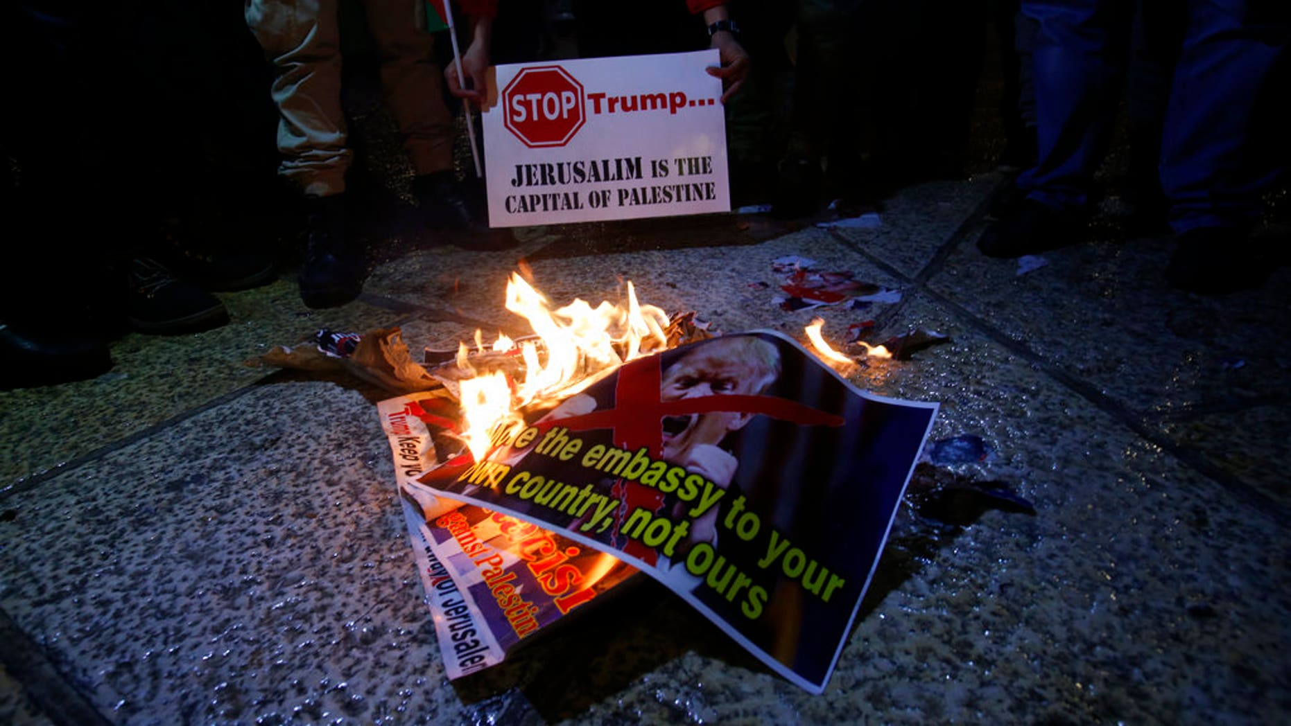 Palestinian burn a poster of the U.S. President Donald Trump during a protest in Bethlehem, West Bank, Wednesday, Dec. 6, 2017. Defying dire, worldwide warnings, President Donald Trump on Wednesday broke with decades of U.S. and international policy by recognizing Jerusalem as Israel's capital.(AP Photo/Nasser Shiyoukhi)