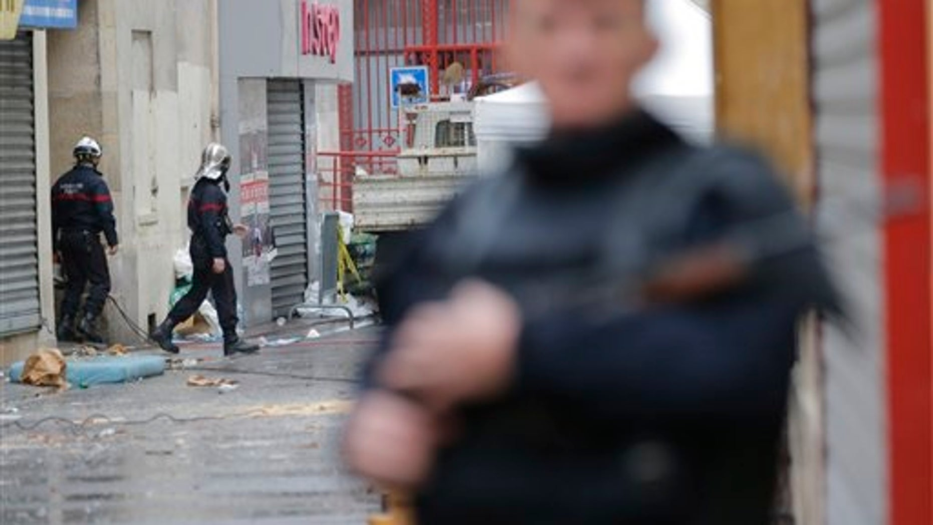 Firemen, left, leave the building of Wednesday's raid on an apartment in Paris suburb Saint-Denis, Thursday Nov.19, 2015. With France still reeling from last week's deadly attacks in Paris, Prime Minister Manuel Valls warned Thursday that Islamic extremists might at some point use chemical or biological weapons, and urged lawmakers to extend a national state of emergency by three months. (AP Photo/Christophe Ena)
