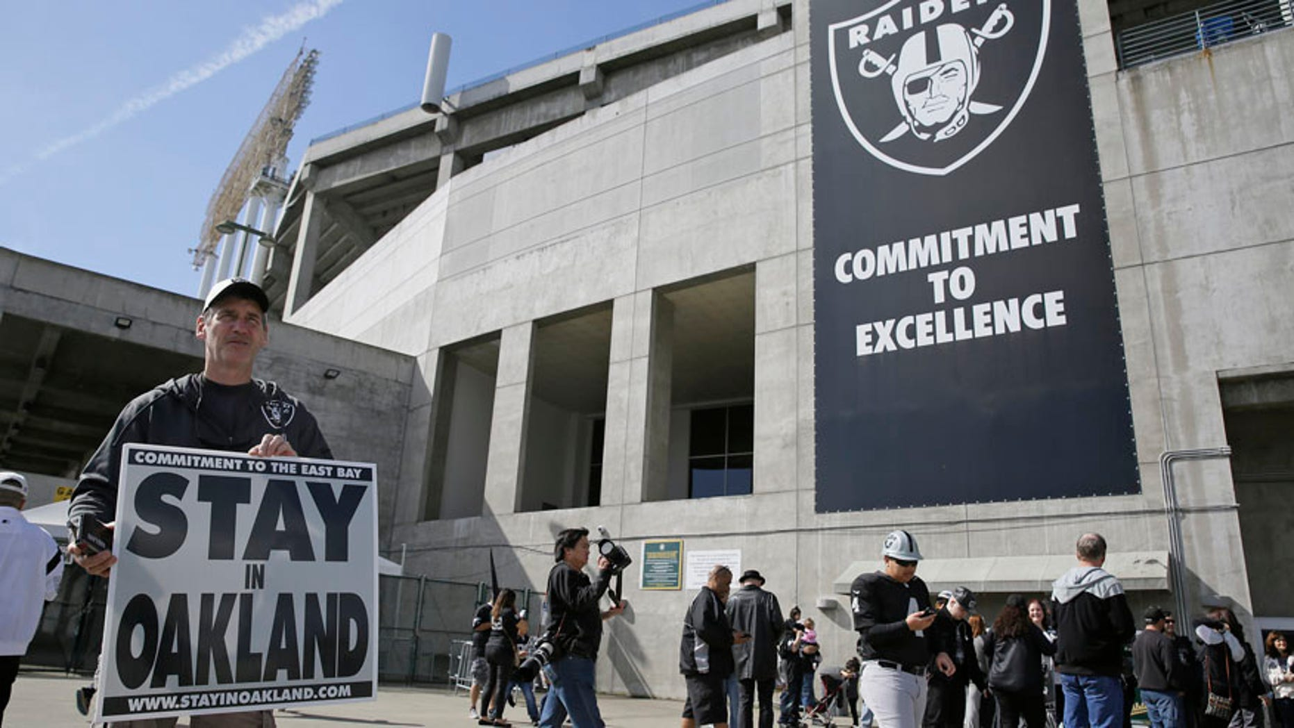 March 25, 2017: John P. Kelleher holds up a sign outside the Oakland Coliseum before the start of a rally to keep the Oakland Raiders from moving.