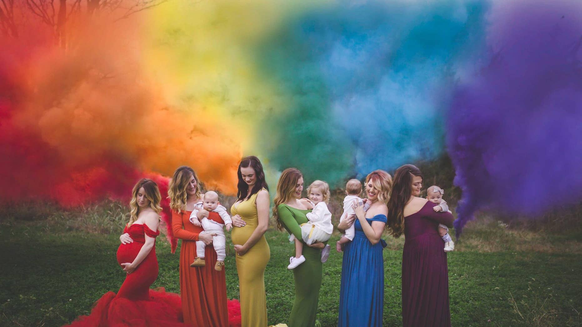 """Six women pose for a photo with their """"rainbow babies,"""" those conceived after miscarriage or stillbirth."""