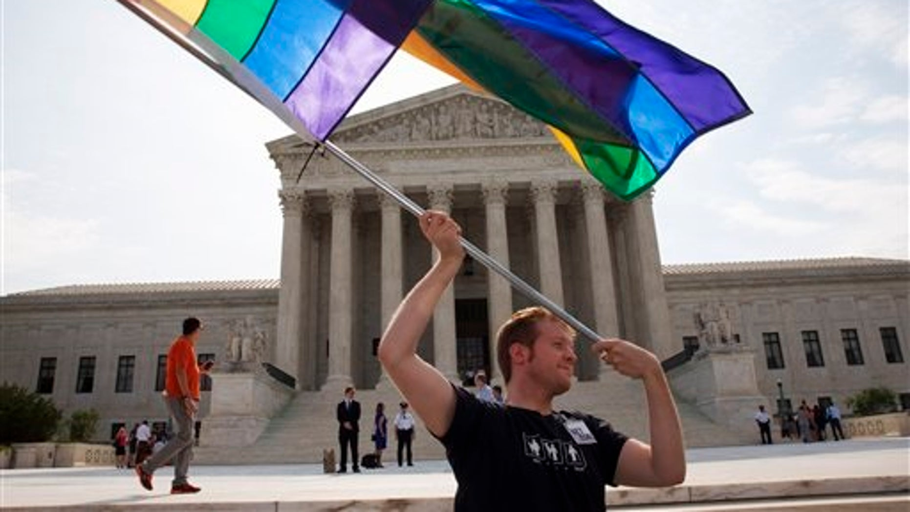 FILE -- June 25, 2015: John Becker, 30, of Silver Spring, Md., waves a rainbow flag in support of gay marriage outside the Supreme Court in Washington. (AP Photo/Jacquelyn Martin)