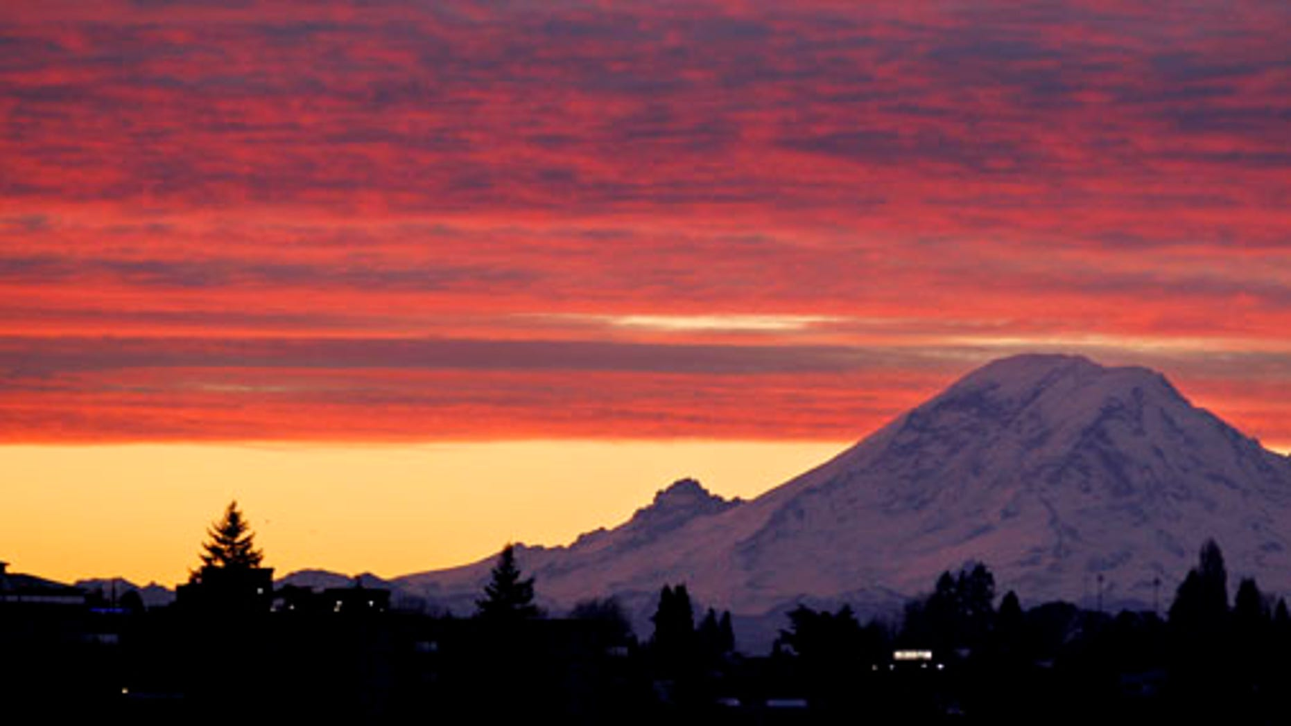 Mount Rainer, a 14,411-foot stratovolcano, is seen at dawn during a colorful sunrise Tuesday, Dec. 13, 2011, from Seattle, some 50 miles away. Generally clear skies are expected through Tuesday in the area, with an increasing chance of showers coming Wednesday, with highs in the low 40's through the week. (AP Photo/Elaine Thompson)