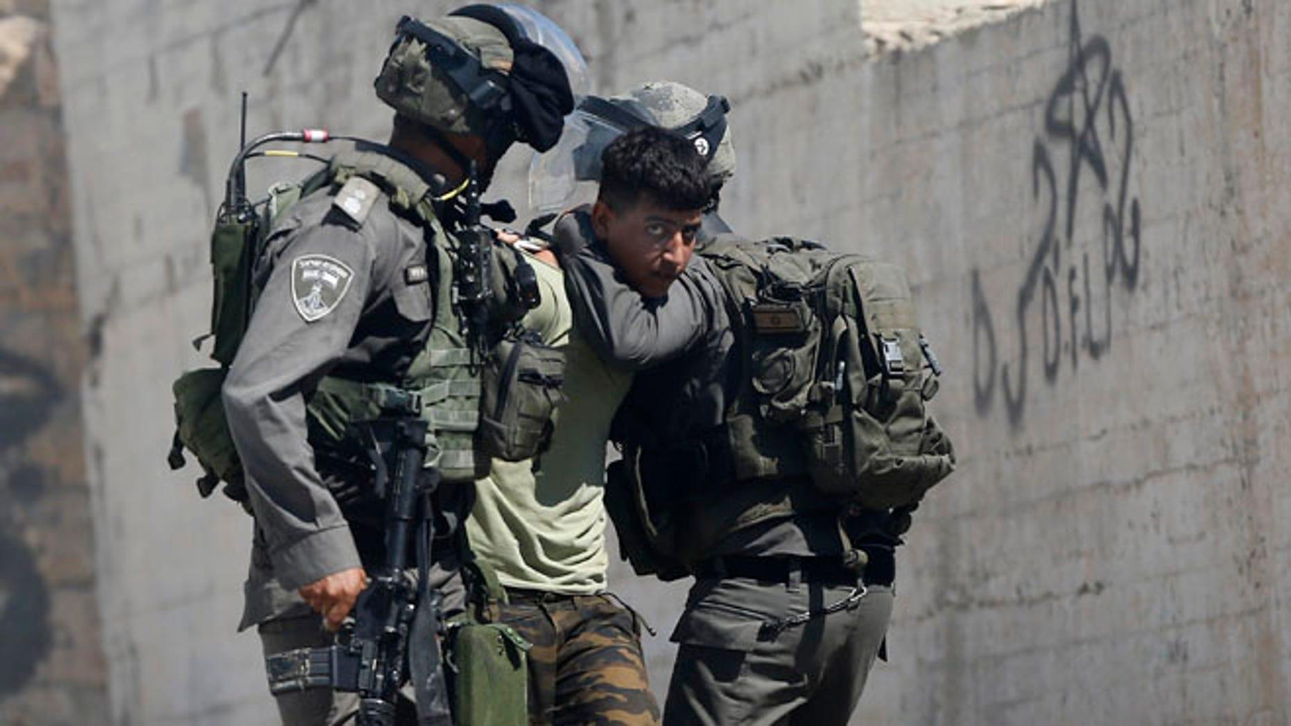 Israeli border police arrest a Palestinian during clashes in the West Bank village of Deir Abu Mash'al near Ramallah, Saturday.