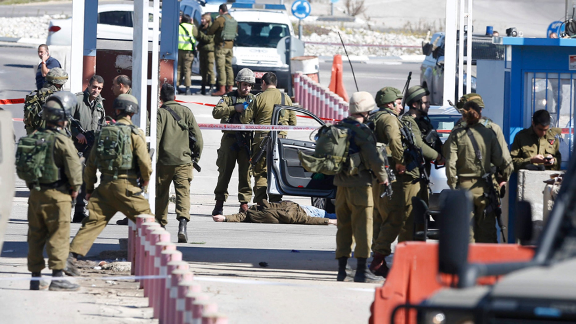Jan. 31, 2016: Israeli security forces inspect the body of a Palestinian identified as Amjad Sukkari, inside a car, at the checkpoint between the city of Ramallah and Jewish settlement of Beit El in the West Bank.