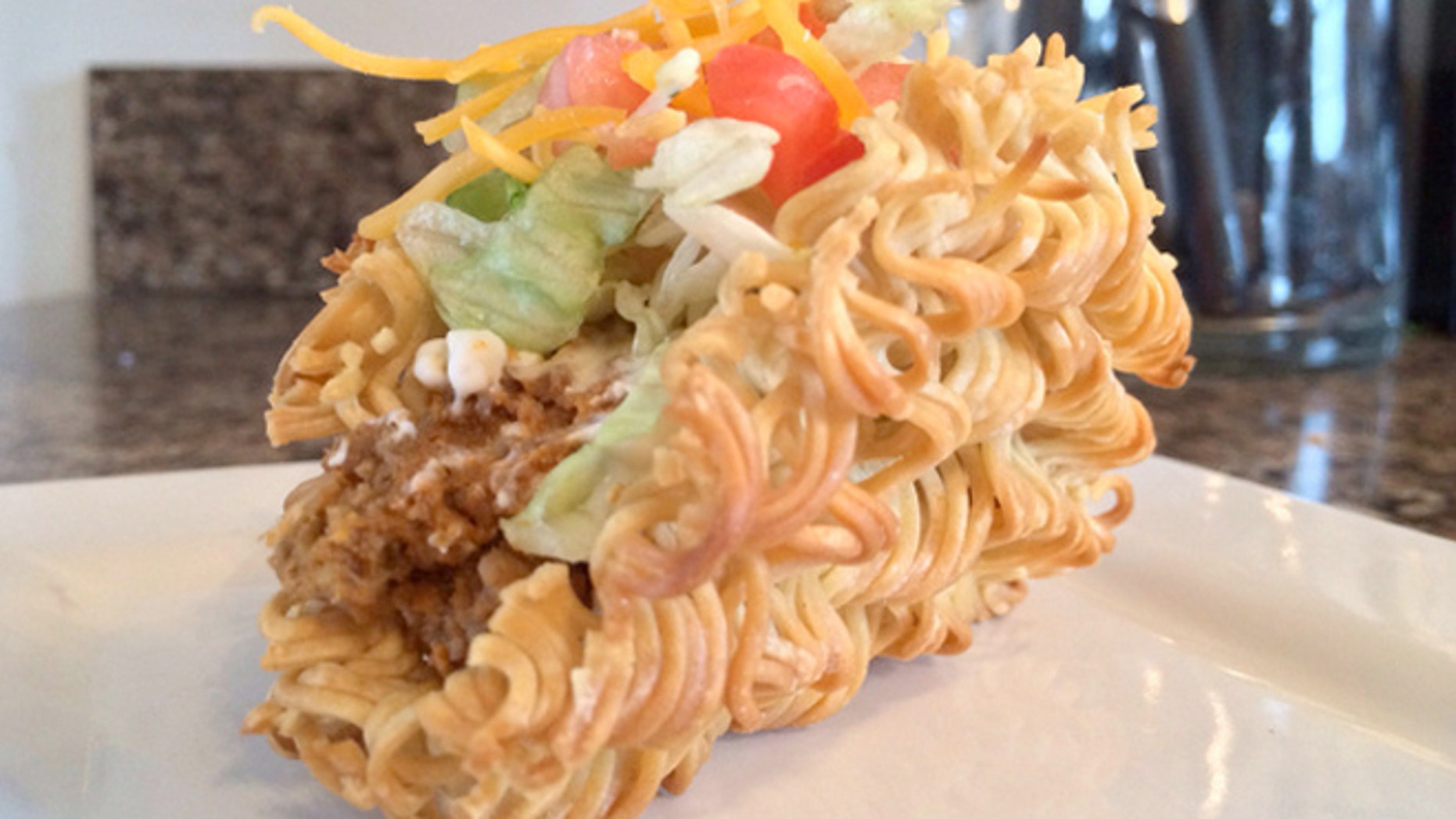 The ramen taco has a ramen noodle shell filled with beef, lettuce, tomatoes, cheese, and sour cream.