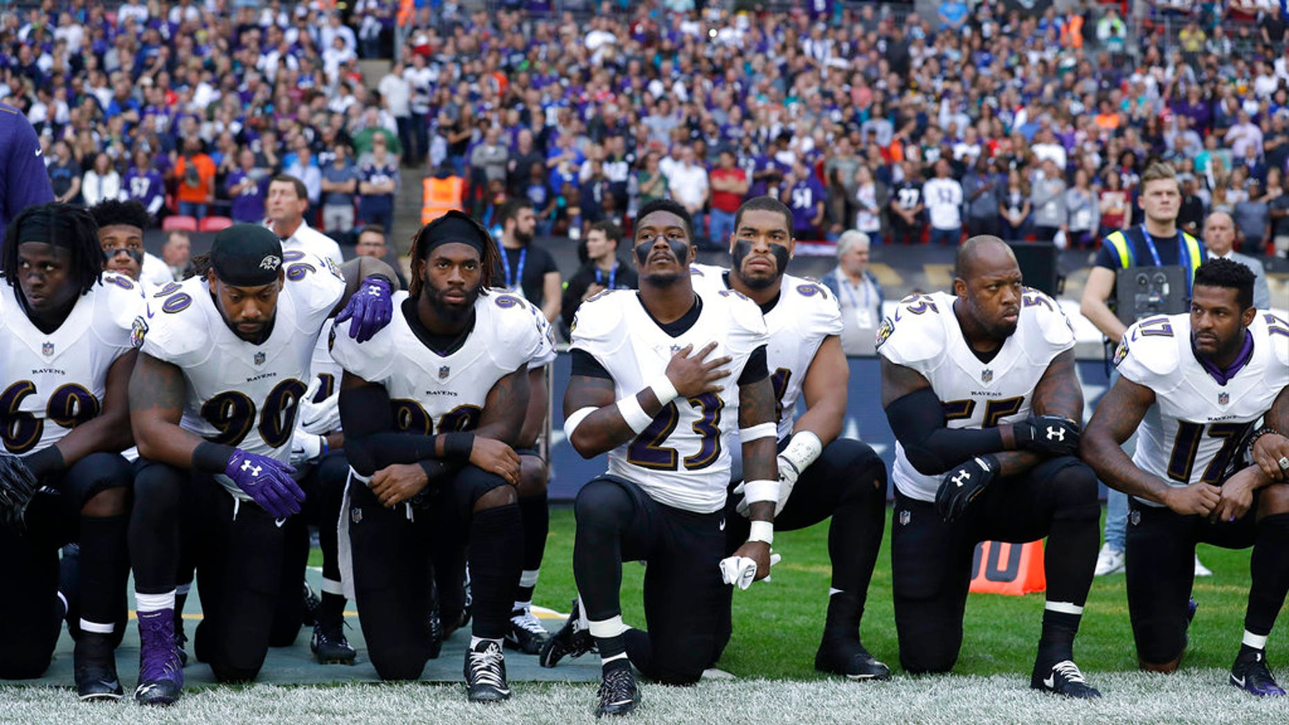 Baltimore Ravens players kneel down during the playing of the U.S. national anthem before an NFL football game against the Jacksonville Jaguars at Wembley Stadium in London, Sunday Sept. 24, 2017. (AP Photo/Matt Dunham)