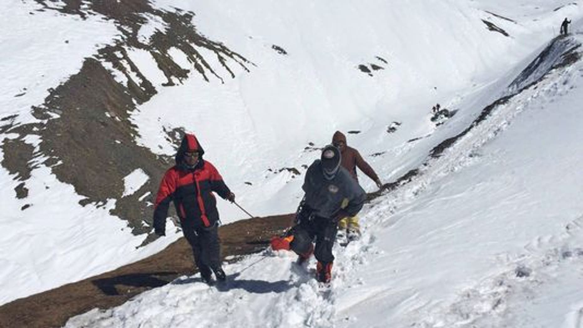Rescue team members carry the body of an avalanche victim at Thorong La pass area in Nepal, on Oct. 17, 2014.