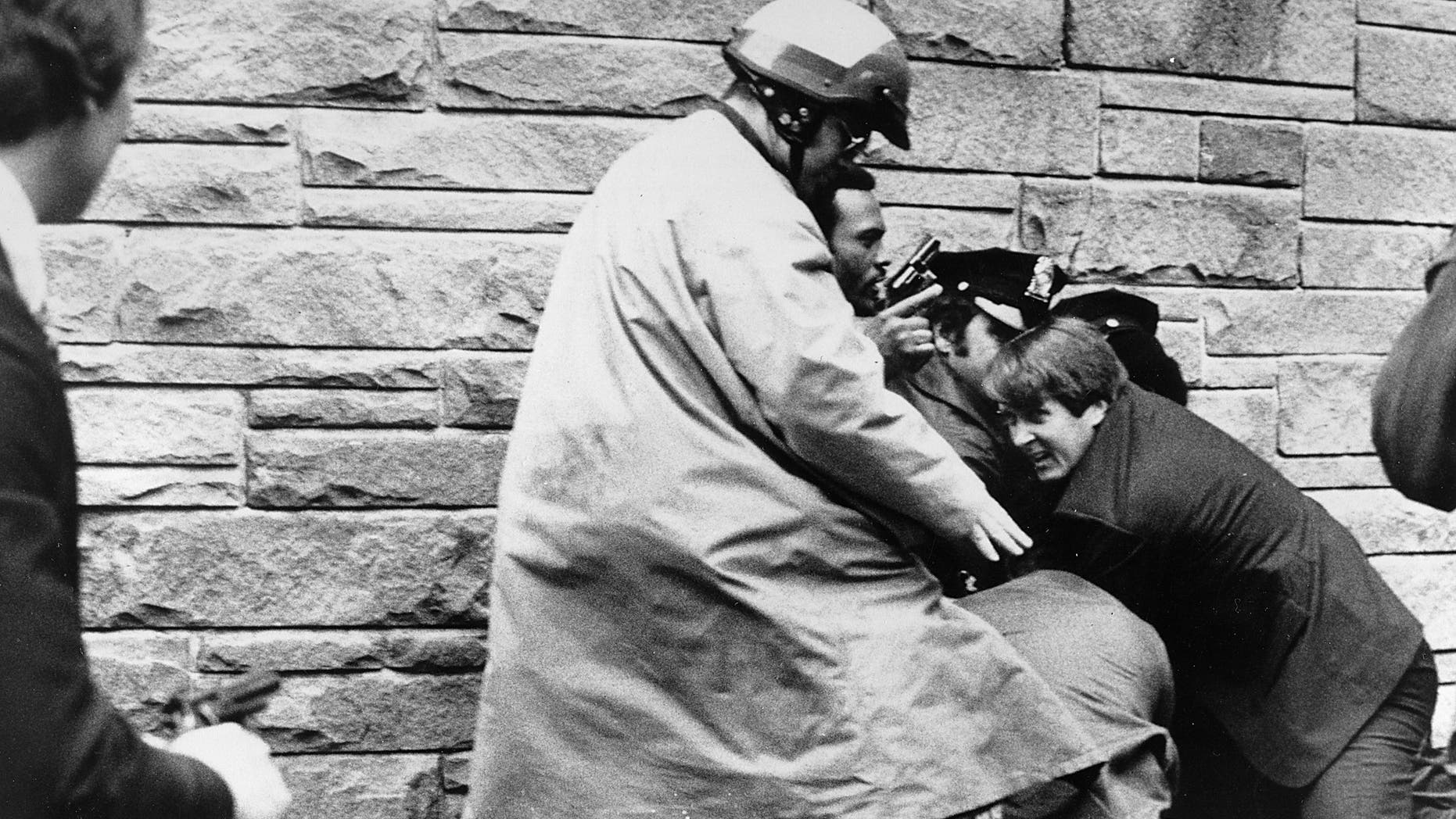 In this March 30, 1981, file photo, White House press secretary James Brady lies wounded on the sidewalk outside a Washington hotel after being shot during an assassination attempt on U.S. President Ronald Reagan, Monday, March 30, 1981.