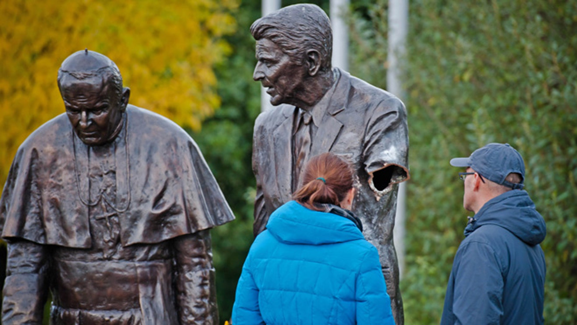 Oct. 1, 2013: Passersbys are seen looking at a former president Ronald Reagan statue with a severed arm in a park in Gdansk, Poland. The bronze statue is a larger than life rendering of Reagan and the Polish born Pope John Paul II, inspired by an AP photograph taken by Scott Stewart during John Paul's visit to the US in 1987 and honors Reagan's support for Poland's struggle to end communism. The police are searching for the vandal who cut the arm off.