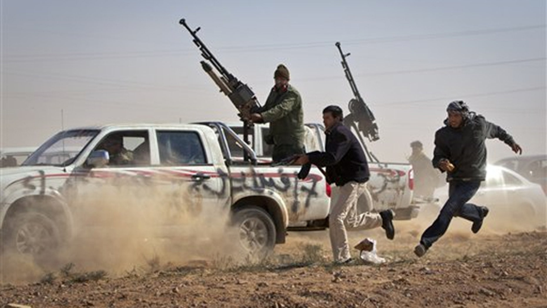 Rebel fighters shoot the tires out of a vehicle, unseen, belonging to Muammar al-Qaddafi's forces as it speeds through the rebel front line east of Brega, Libya, April 3.