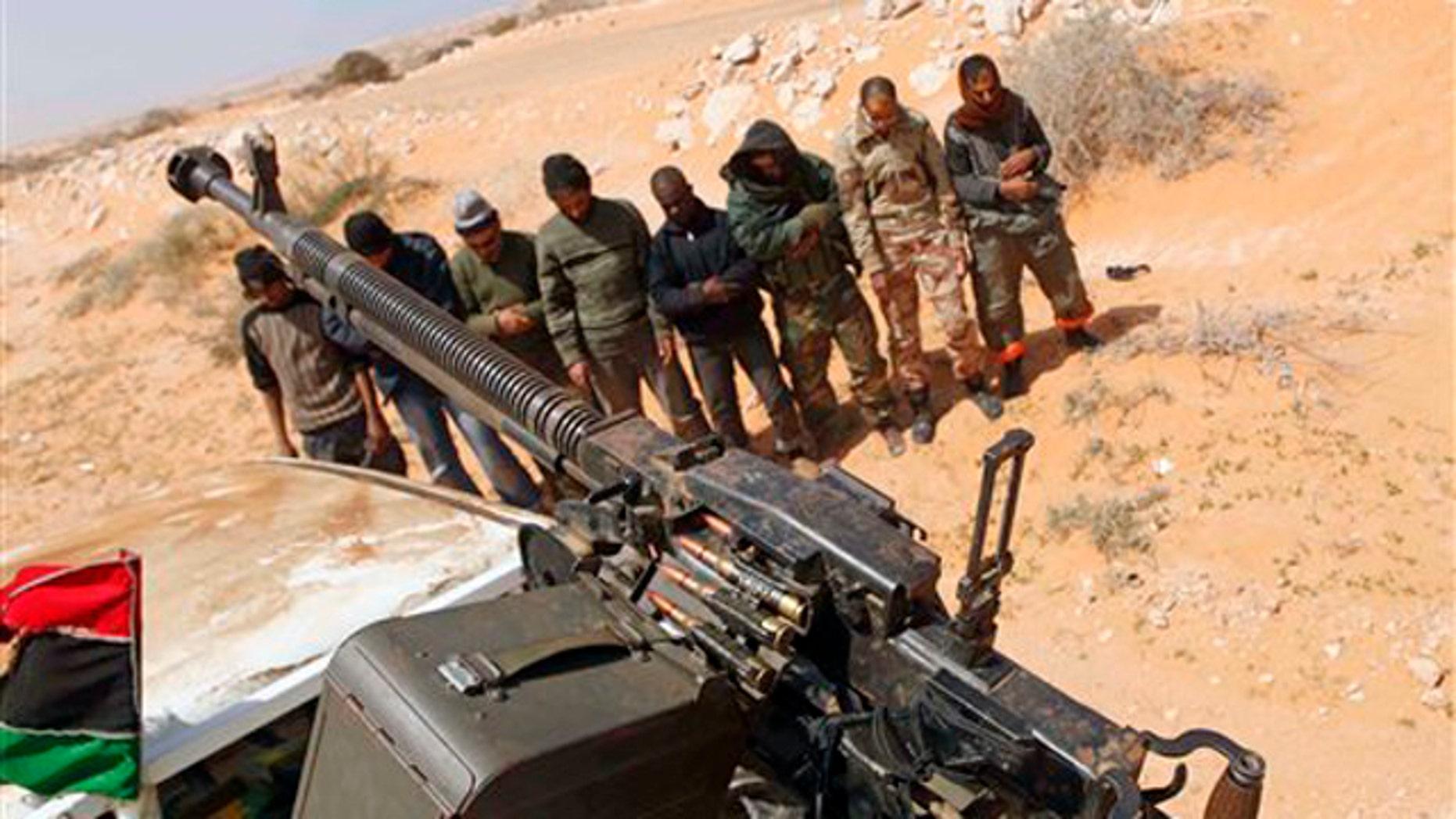 Libyan rebels pray 75 miles east of Sirte in eastern Libya March 28.
