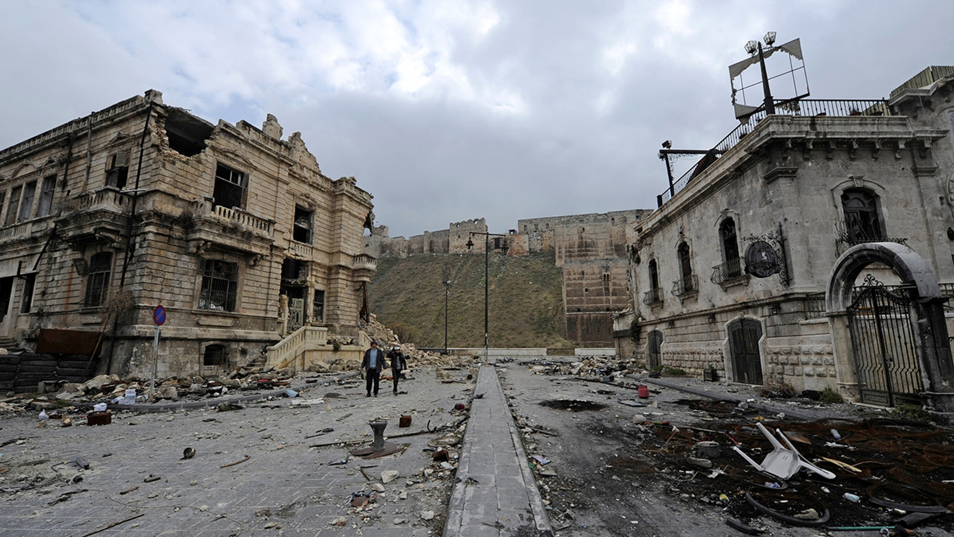 People walk past the old customs buildings (L) and Peoria restaurant (R) near Aleppo's historic citadel, in the government controlled area of the city, Syria December 17, 2016. REUTERS/Omar Sanadiki - RC1A5D700FD0
