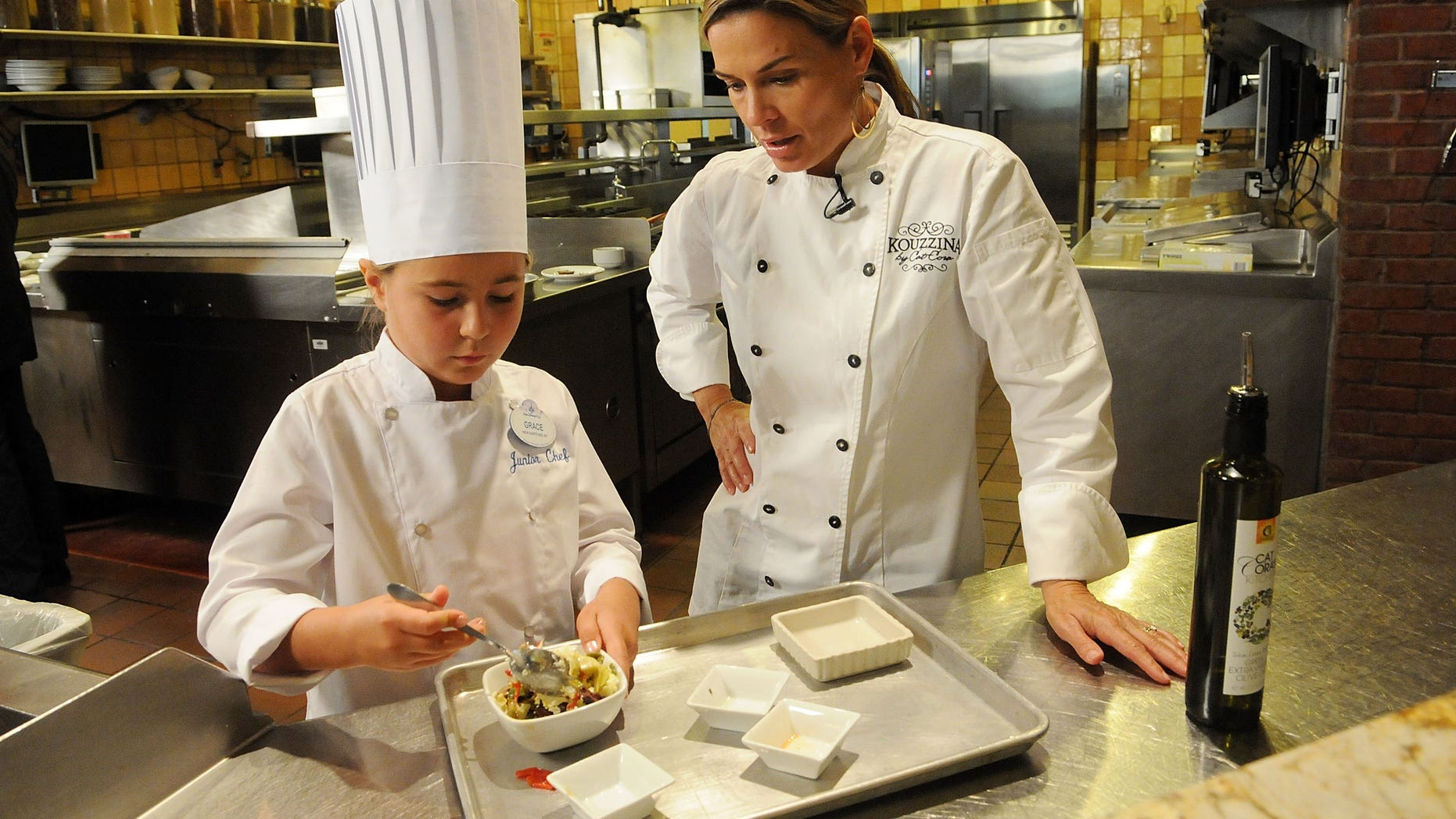 "ORLANDO, FL - OCTOBER 04:  Celebrity Chef Cat Cora (R) cooks with Grace LaFountain, the winner of the national Loukoumi's celebrity cookbook ""Favorite Childhood Recipe"" contest at Cat's Restaurant Kouzzina on The BoardWalk at The Walt Disney World resort on October 4, 2012 in Lake Buena Vista, Florida.  (Photo by Gerardo Mora/Getty Images for NK Publications, Inc.)"