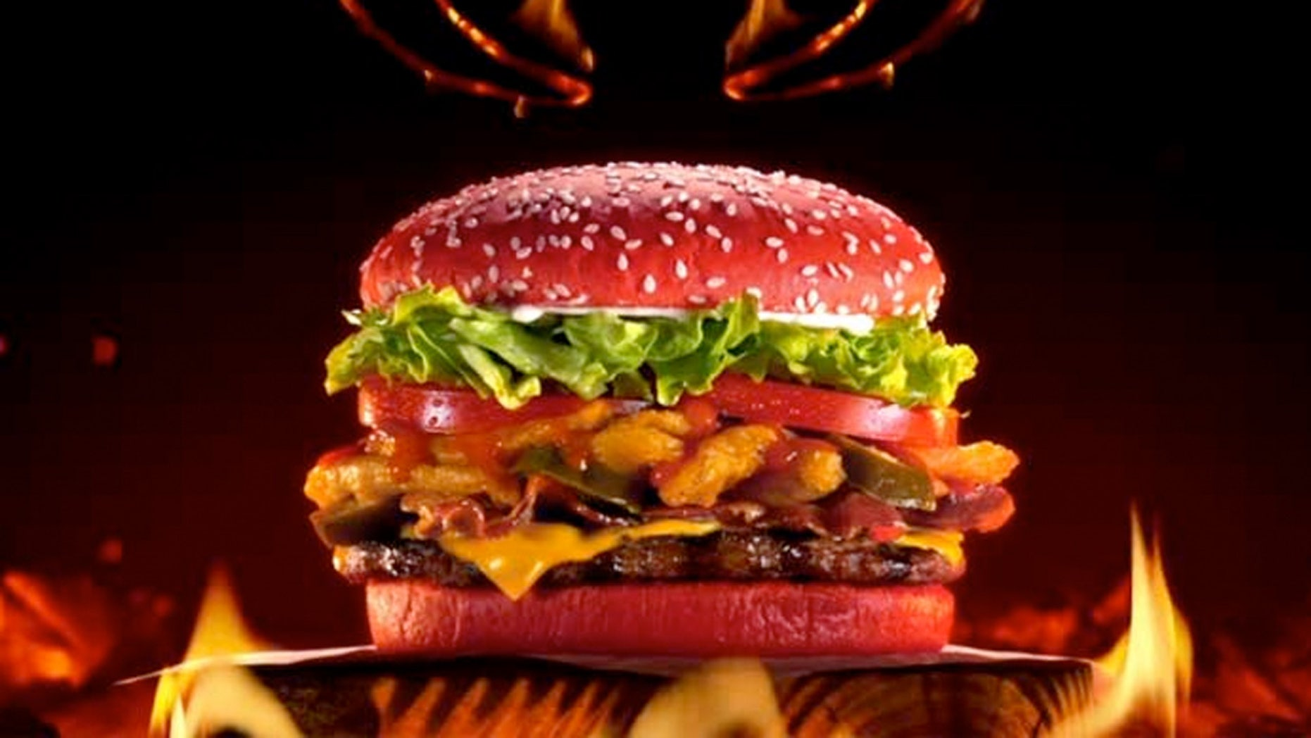 """The Angriest Whopper will consist of """"flame-grilled beef, piled high with thick-cut bacon, American cheese, iceberg lettuce, tomatoes, crispy onion petals, jalapeños, creamy mayonnaise and spicy angry sauce all layered between a fiery red bun that has hot sauced baked in."""