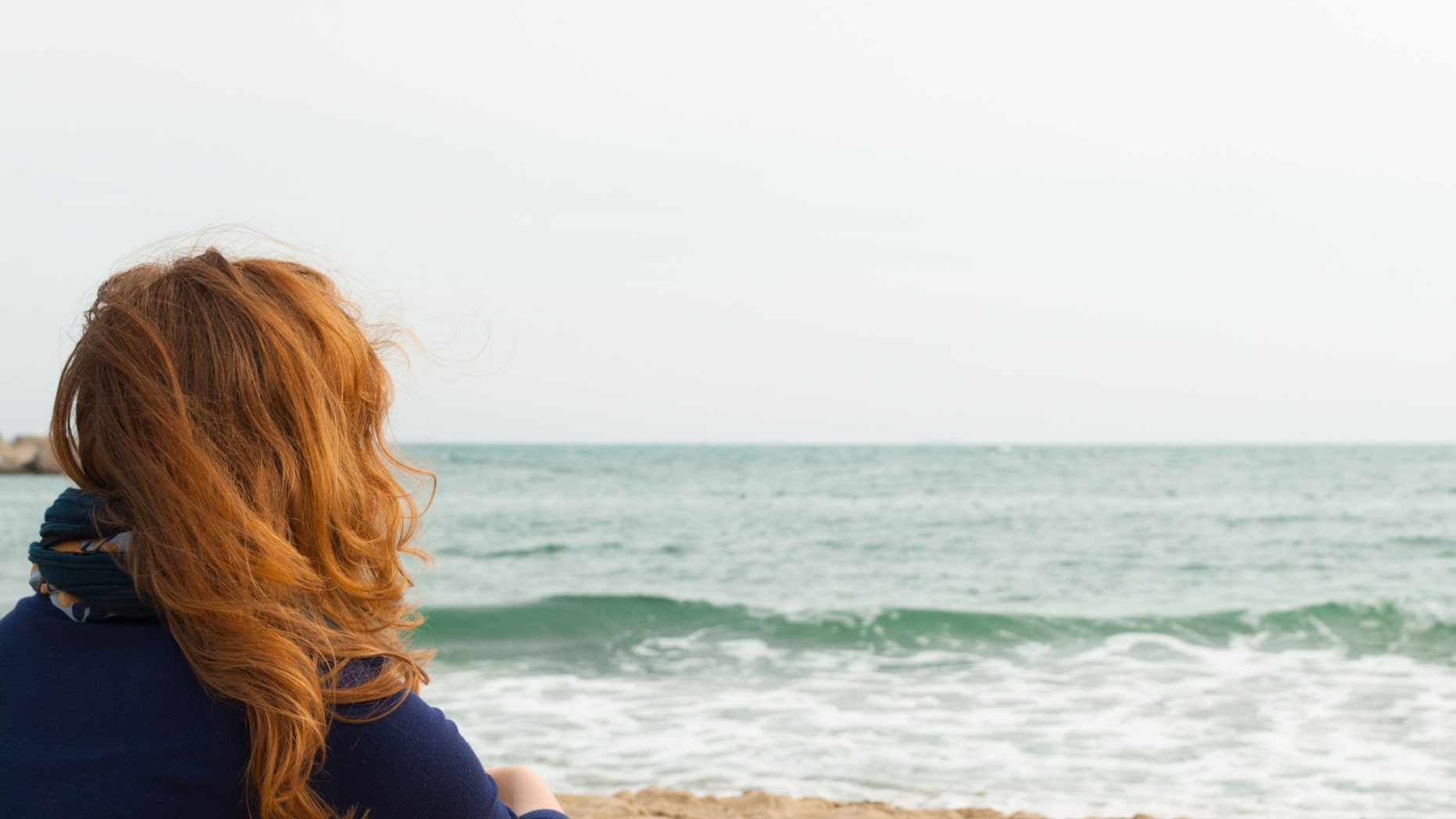 Redhead girl on a Barcelona sand beach looking at the sea, view from behind