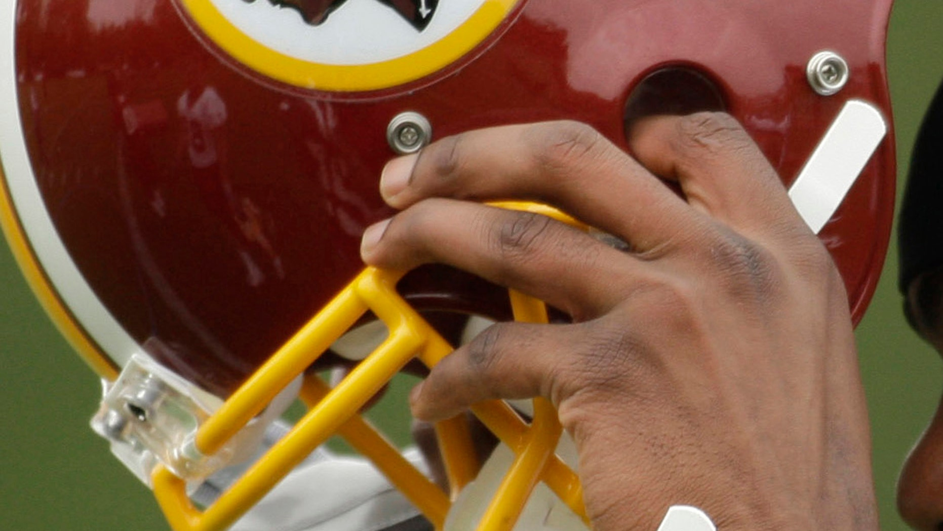 In this file photo, Washington Redskins Marko Mitchell puts his helmet on during their NFL football minicamp practice at their training facility in Ashburn, Va.