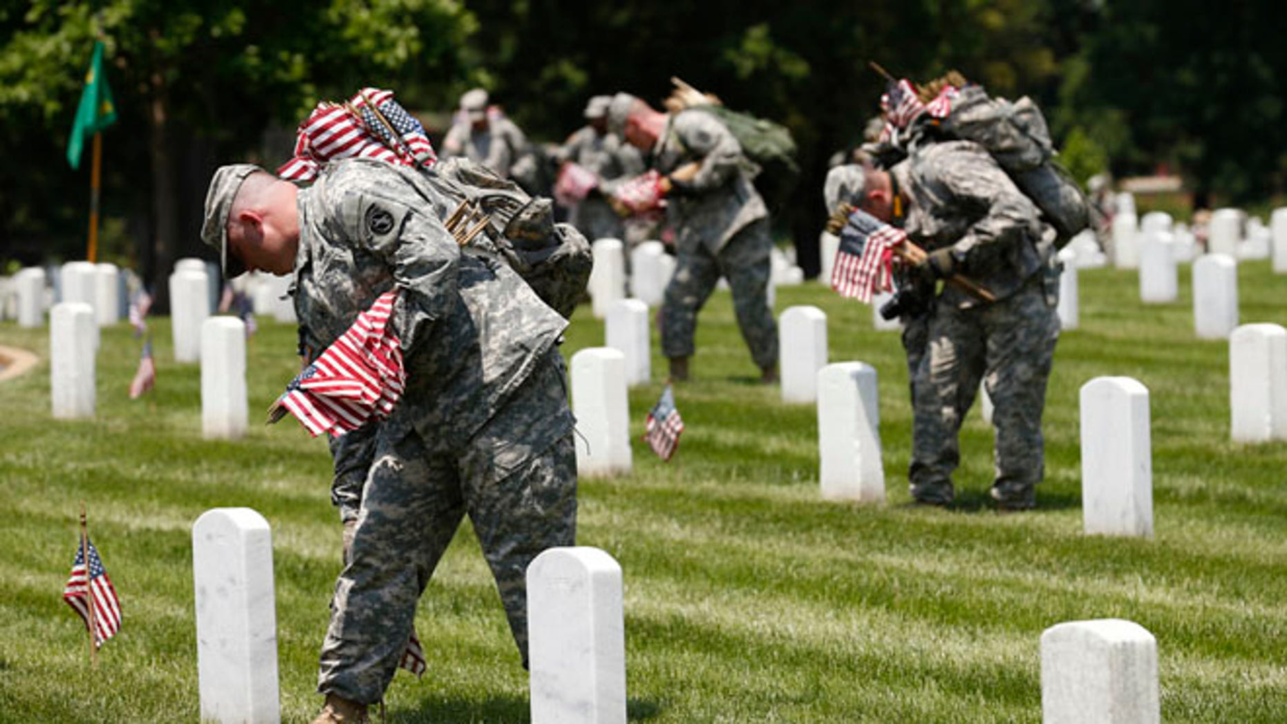 """Members of the Third U.S. Infantry Regiment (The Old Guard) take part in a """"Flags-In"""" ceremony, ahead of Memorial Day, at Arlington National Cemetery in Washington May 22, 2014."""
