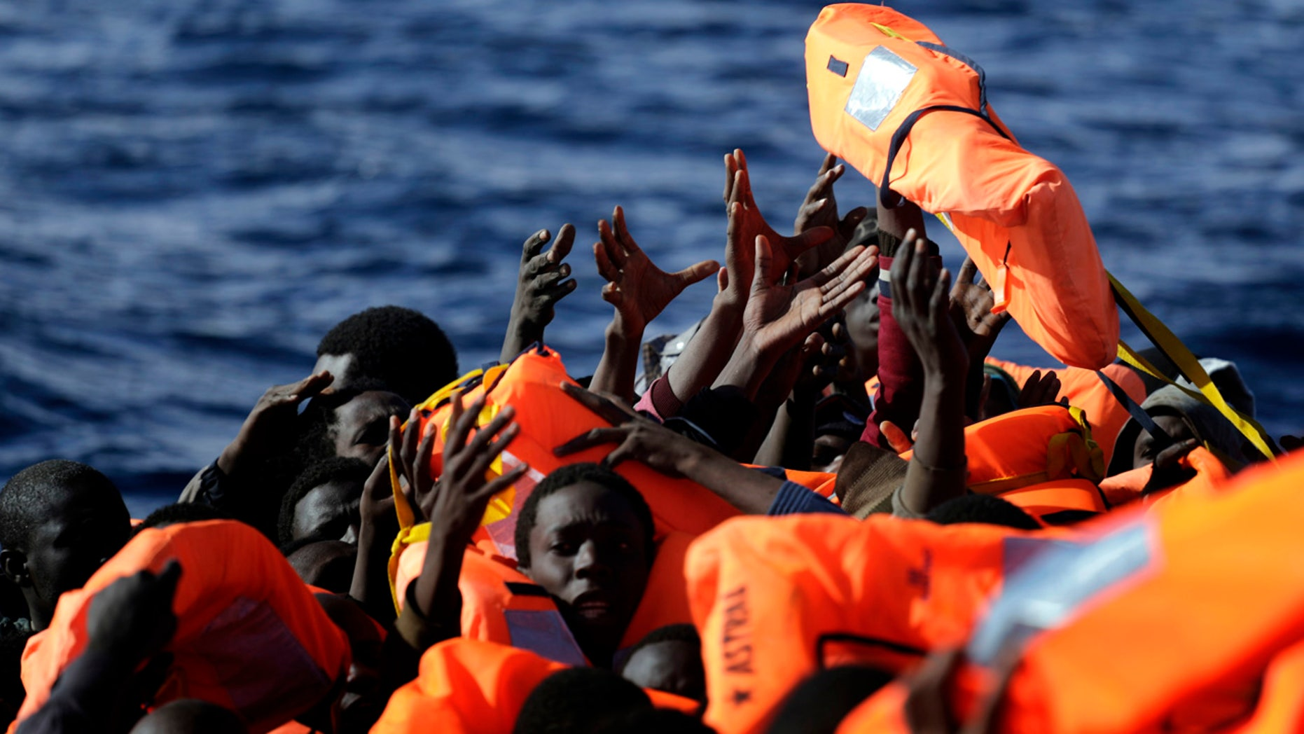 Jan. 27, 2017: Sub-Saharan migrants raise their hands to grab a life jacket as they are rescued by members of the Proactive Open Arms NGO, in the Mediterranean Sea north of Zumarah, Libya.