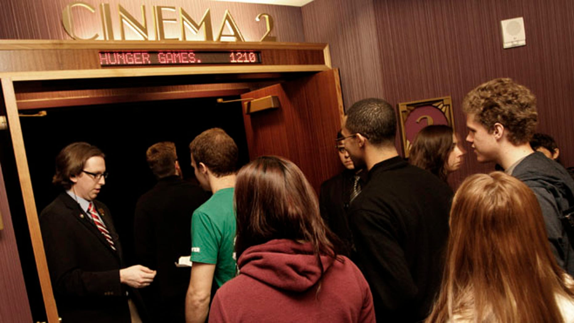 Workers for Regal Entertainment Group, like the one seen here collecting tickets from movie-goers, have had their work weeks shortened in a new company-wide mandate. Internal documents obtained by FoxNews.com show that the cuts were enacted in response to the Affordable Care Act.