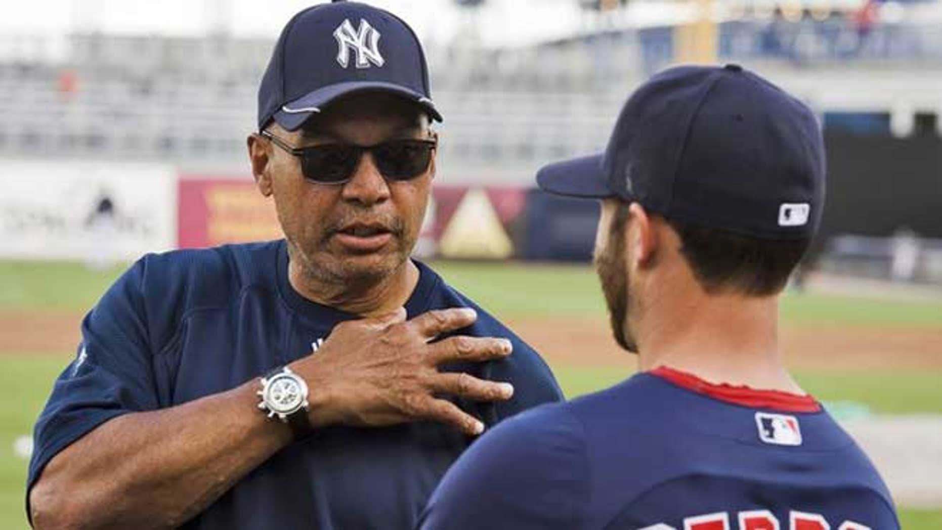 March 13, 2012: New York Yankees Hall of Famer Reggie Jackson (L) talks with Boston Red Sox infielder Dustin Pedroia during workouts before a spring training baseball game in Tampa, Florida.