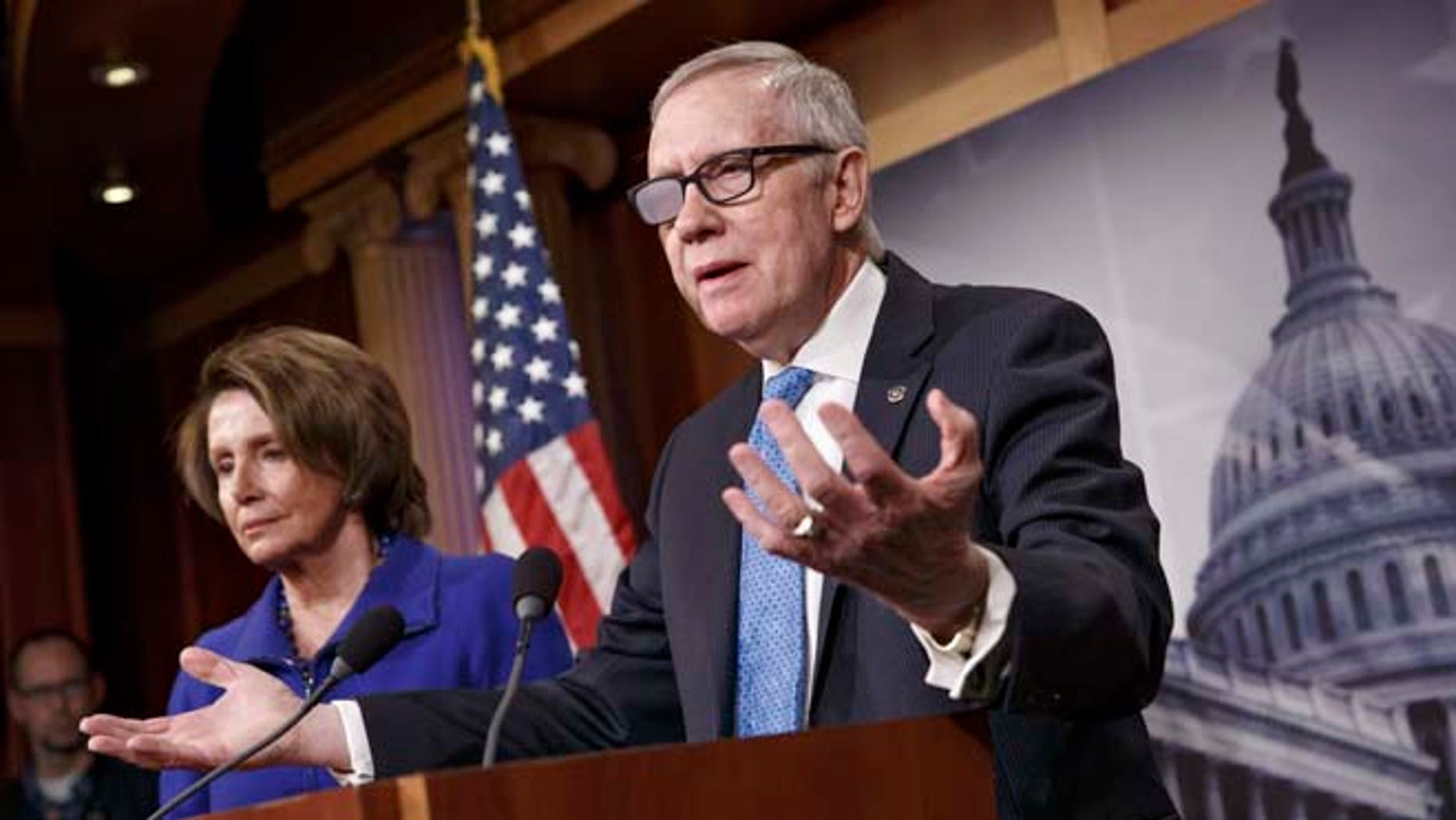 Feb. 26, 2015: Senate Minority Leader Harry Reid of Nev., accompanied by House Minority Leader Nancy Pelosi of Calif., gestures during a news conference on Capitol Hill.