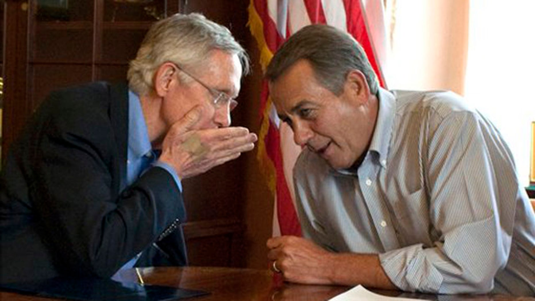 Senate Majority Leader Harry Reid holds his hand up as he whispers to House Speaker John Boehner during a photo opportunity in the House Speaker's office in Washington July 23.