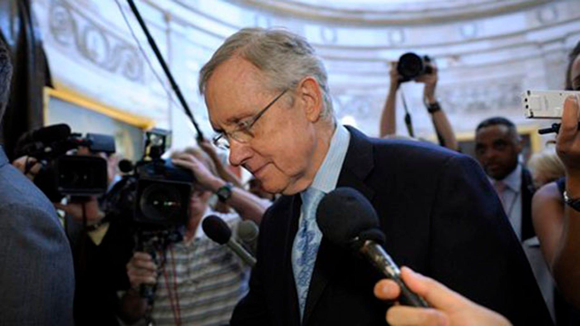 Senate Majority Leader Harry Reid is followed by reporters as he walks through the Capitol Rotunda on Capitol Hill July 31.