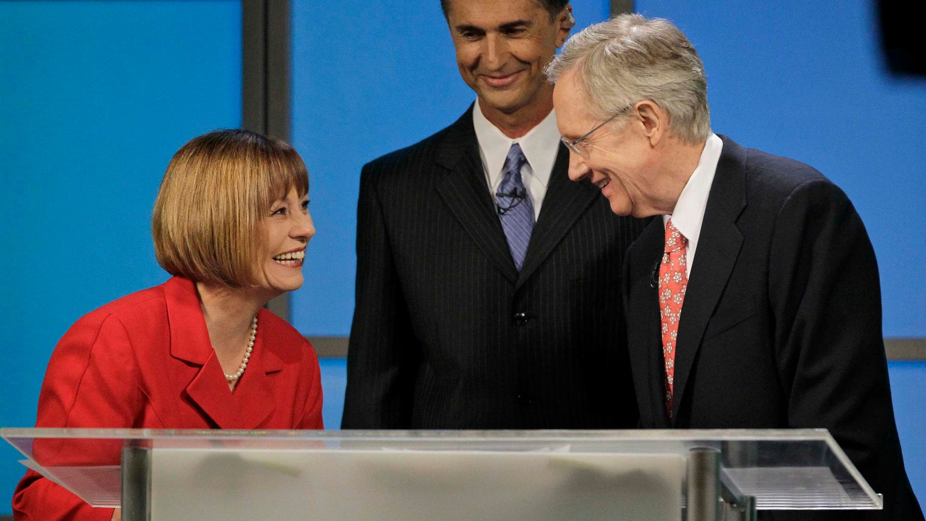 FILE - In this Oct. 14, 2010, file photo Republican Senate candidate Sharron Angle, left, and Democrat Senate Majority Leader Harry Reid talk after their televised Nevada Senate debate in Las Vegas as moderator Mitch Fox smiles. Senate races are extremely close in West Virginia and Nevada, where Reid is battling tea party-backed Angle in a bitter and costly campaign.  (AP Photo/Julie Jacobson, File)