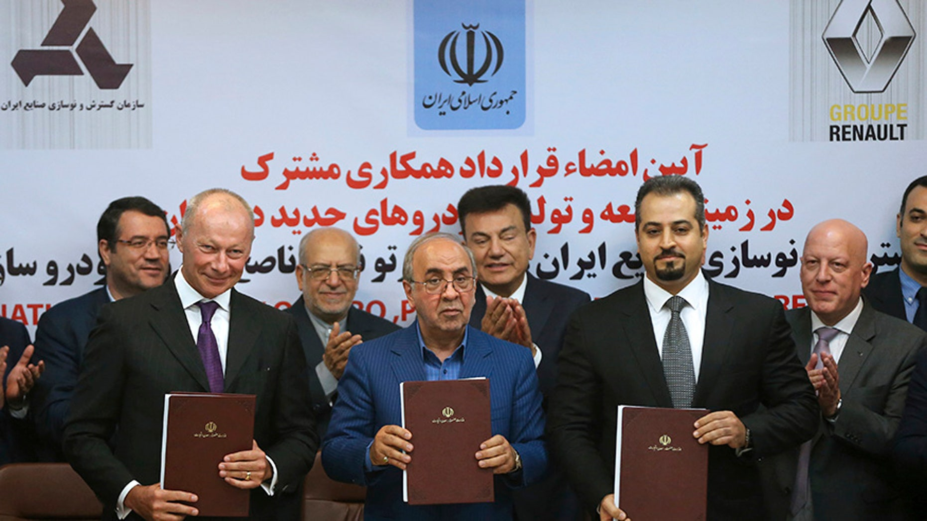 Chief Competitive Officer of Groupe Renault Thierry Bolloré, left, Chairman of Industrial Development and Renovation Oraganization of Iran, IDRO, Mansour Moazami, center, and Negin Group CEO Kourosh Morshed Solouk join shows documents to media after signing a deal in Tehran, Iran, Monday, Aug. 7, 2017. Iran signed the country's biggest-ever car deal with French multinational automobile manufacturer Groupe Renault on Monday to produce 150,000 cars, beginning in 2018. (AP Photo/Vahid Salemi)