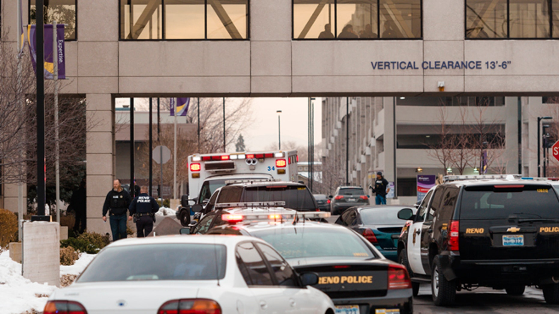 Dec. 17, 2013: Officers gather in front of the Renown Regional Medical Center after a lone gunman shot and injured three people, one fatally, before killing himself in Reno, Nev.