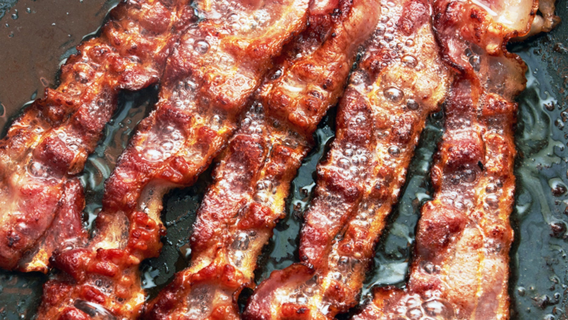 Bacon slice being cooked in frying pan. Close up.