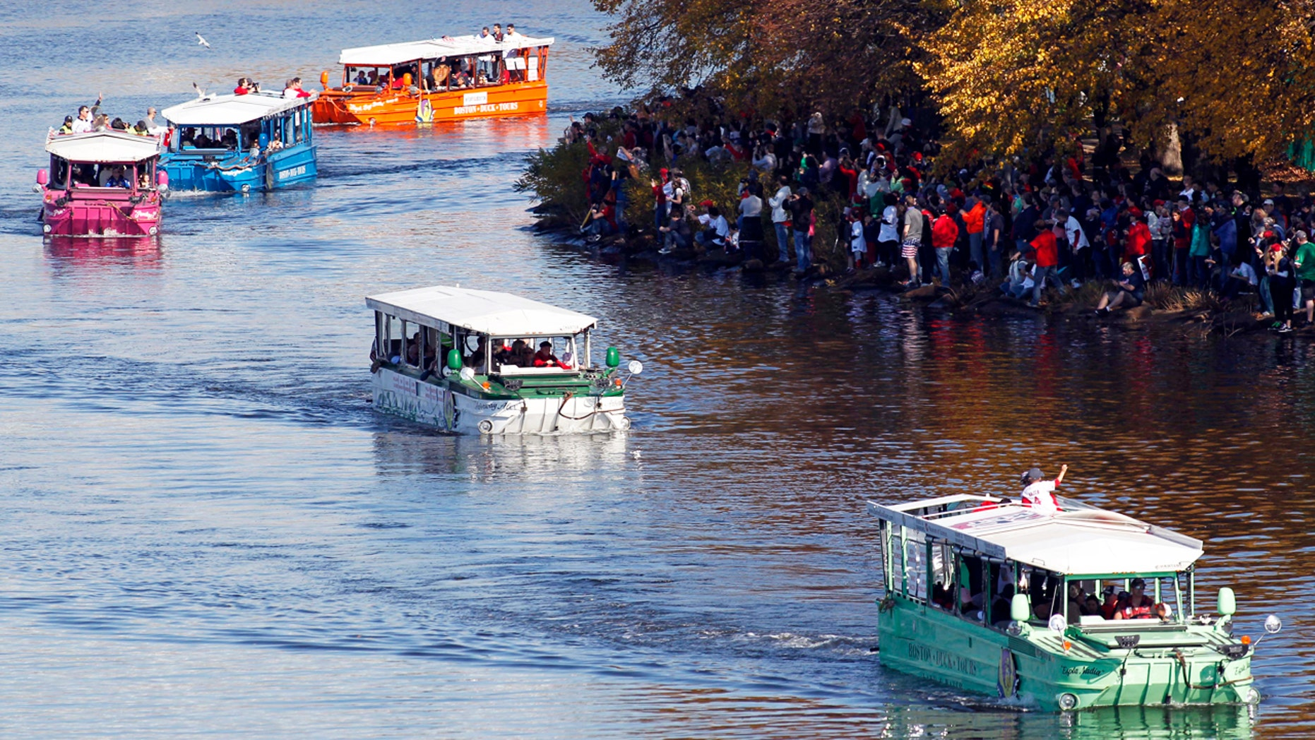 Boston Red Sox fans cheer on members of the team as they ride duck boats down the Charles River during the 2013 World Series parade and celebration.