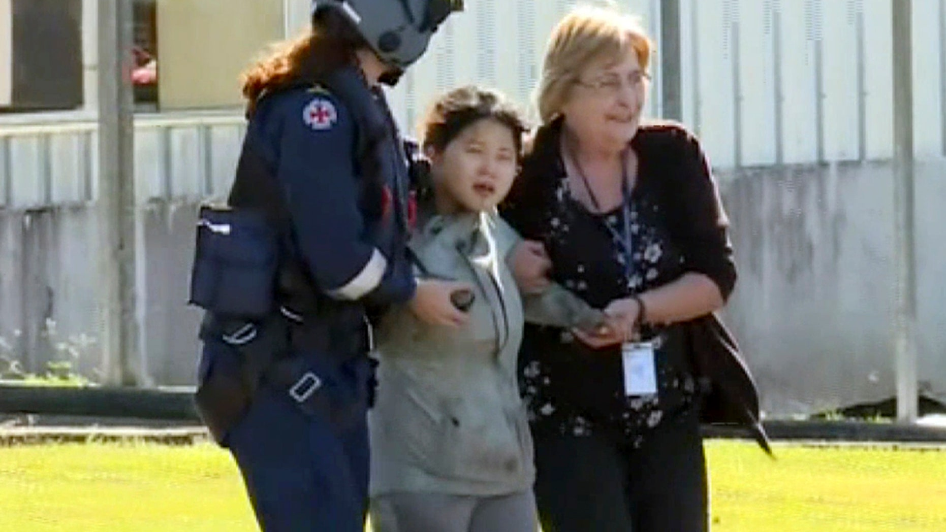 In this image taken from the Australian Broadcasting Corporation video, South Korean backpacker Joohee Han, 25, center, is assisted to a hospital after being rescued by helicopter, Thursday, June 7, 2018, in Tully, Queensland, Australia.