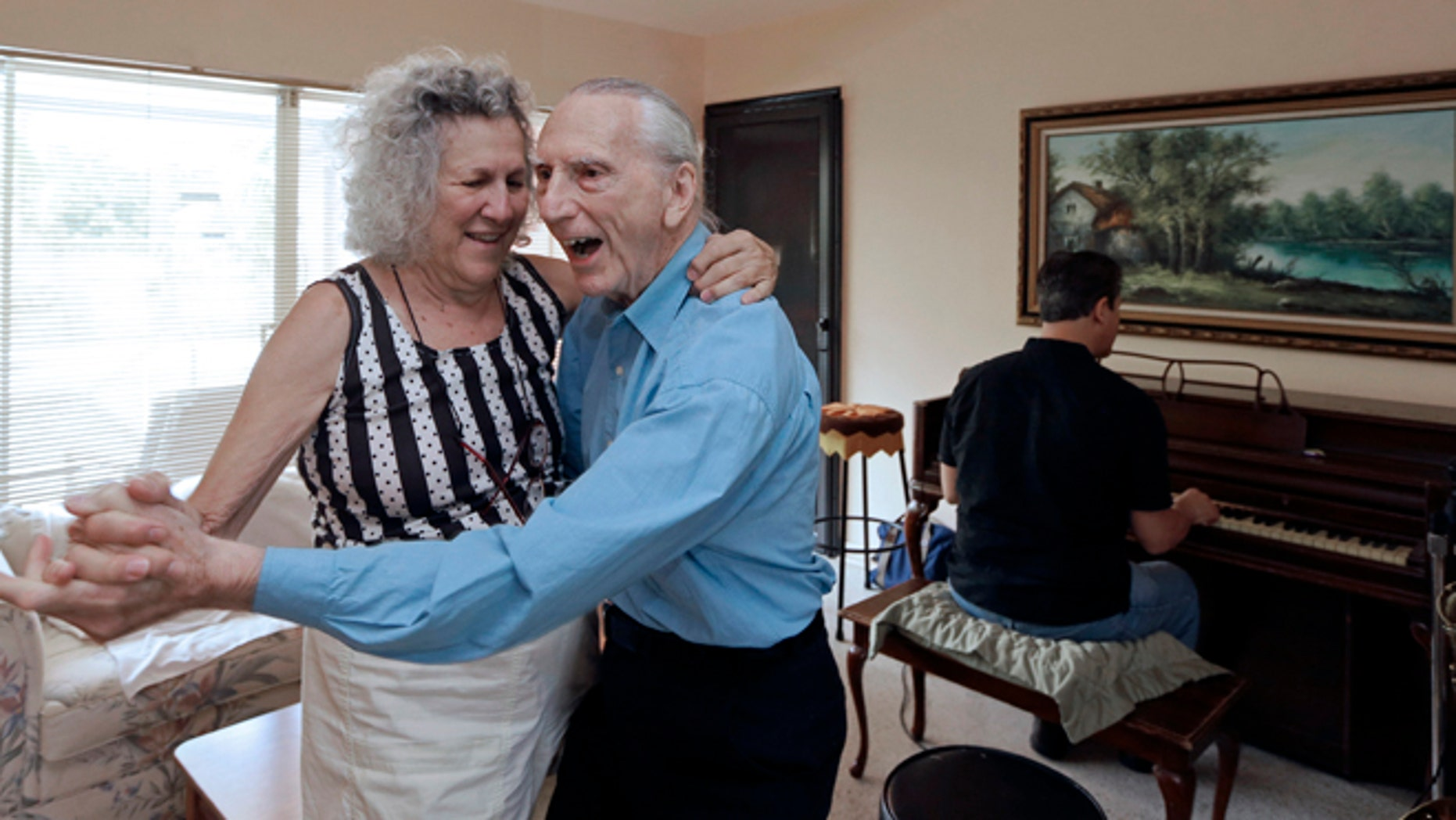 MAY 11: Al Karp, right foreground, and his wife Saundra, left, dance to the music their son Larry, background, plays on the piano at their home in North Miami Beach, Fla.