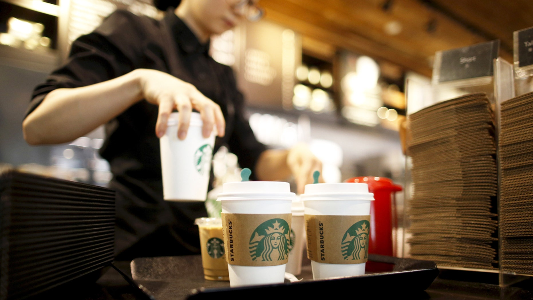 A staff serves beverages at a Starbucks coffee shop in Seoul, South Korea, in this March 7, 2016, file photo. REUTERS/Kim Hong-Ji/Files  GLOBAL BUSINESS WEEK AHEAD PACKAGE - SEARCH 'BUSINESS WEEK AHEAD APRIL 18'  FOR ALL IMAGES - RTX2AE8U