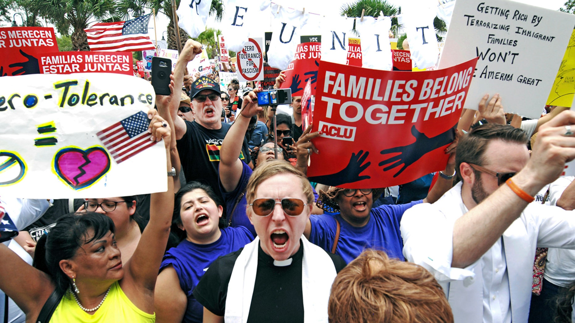 """In this June 28 photo, protesters chant, """"Families belong together!"""" as they walk to the front doors of the federal courthouse in Brownsville, Texas."""