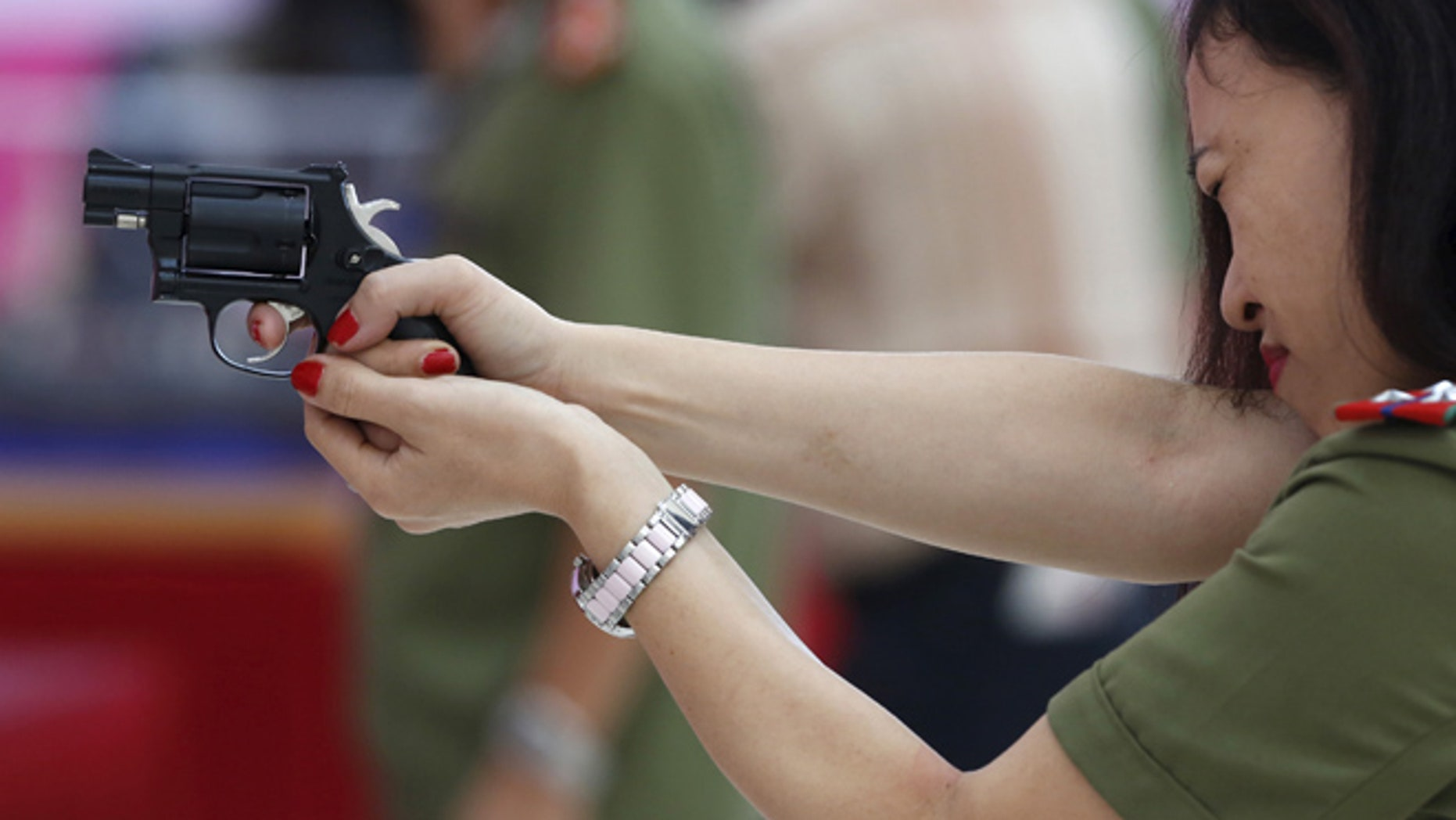 A policewoman demonstrates a Vietnamese-made pistol during celebrations to commemorate the 70th anniversary of the establishment of the Vietnam Public Security police force at the National Convention Center in Hanoi August 18, 2015. The Vietnam Police force was founded on August 19, 1945, the day of the anti-colonial people's uprising known as the August Revolution. REUTERS/Kham - RTX1OLM6