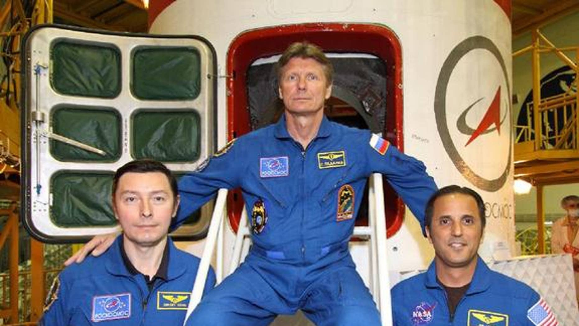 """Sergei Revin (left), Gennady Padalka (center) and Joe Acaba (right) pose in front of the hatchway to their Soyuz TMA-04M spacecraft as they completed their final """"fit check"""" inspection of the vehicle on May 11, 2012. The three will launch toward the space station on May 14."""