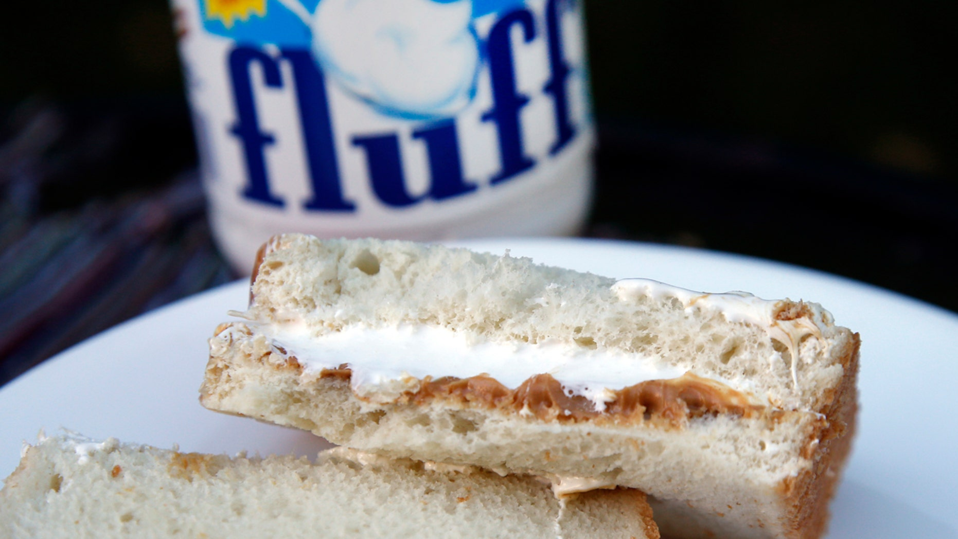In this Sept. 27, 2013, file photo, a jar of Marshmallow Fluff and a Fluffernutter sandwich are displayed in North Andover, Mass. Archibald Query invented Fluff in 1917 in the Boston suburb of Somerville. The marshmallow concoction that's been smeared on a century's worth of sandwiches has inspired a festival and other sticky remembrances as it turns 100 in 2017. (AP Photo/Elise Amendola, File)