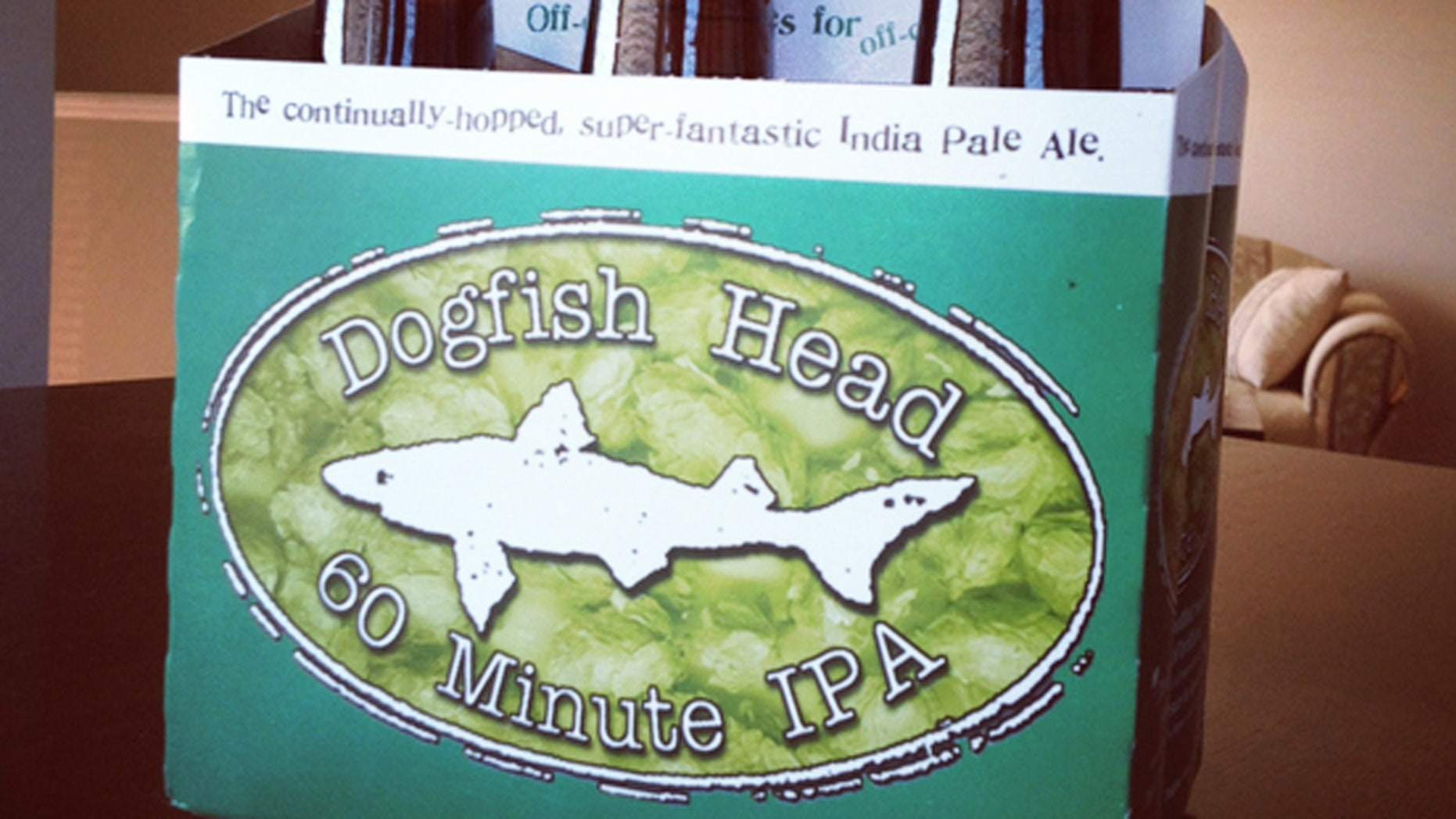 """Dartmouth, Nova Scotia, Canada - August 29, 2012: A six-pack of Dogfish Head 60 Minute IPA Beer sitting on a table inside a home.  All six bottles are visible and unopened with Dogfish Head logo displayed on box.  """"Continually hopped, super-fantastic India Pale Ale"""" is also displayed."""
