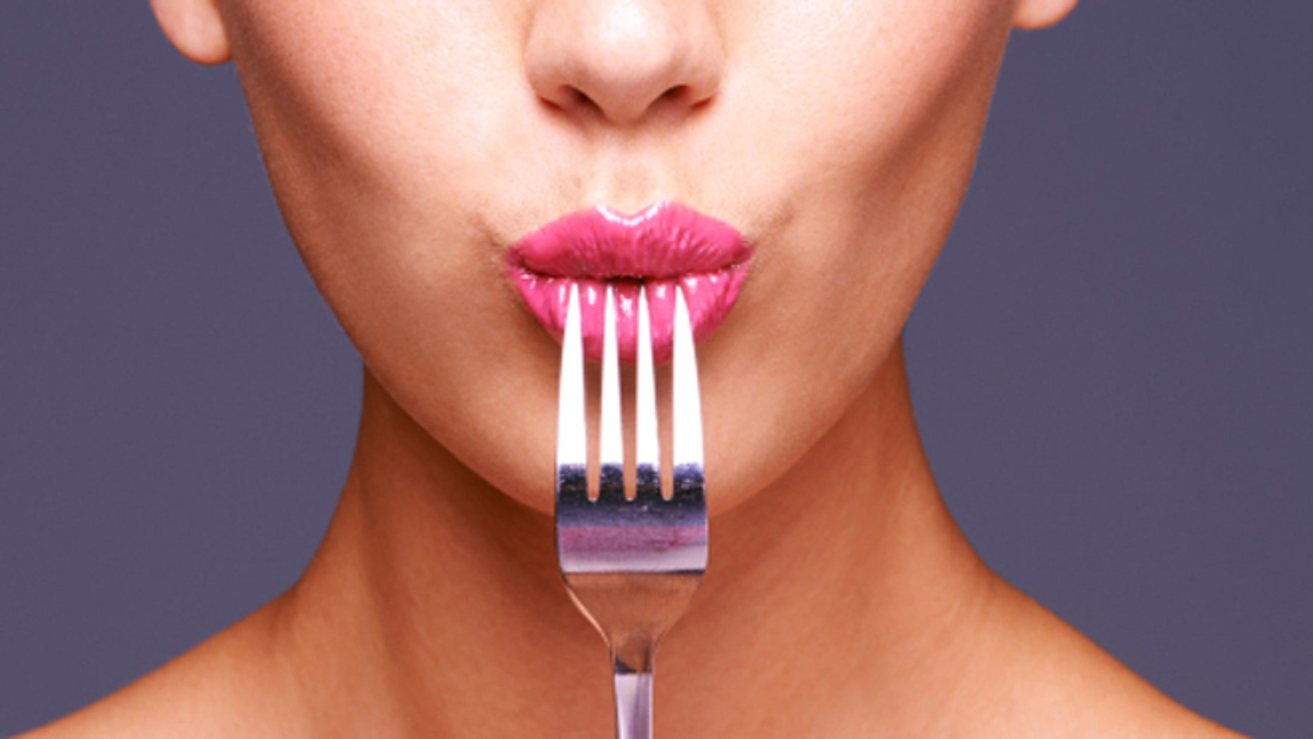 Shot of a beautiful young woman biting on a fork