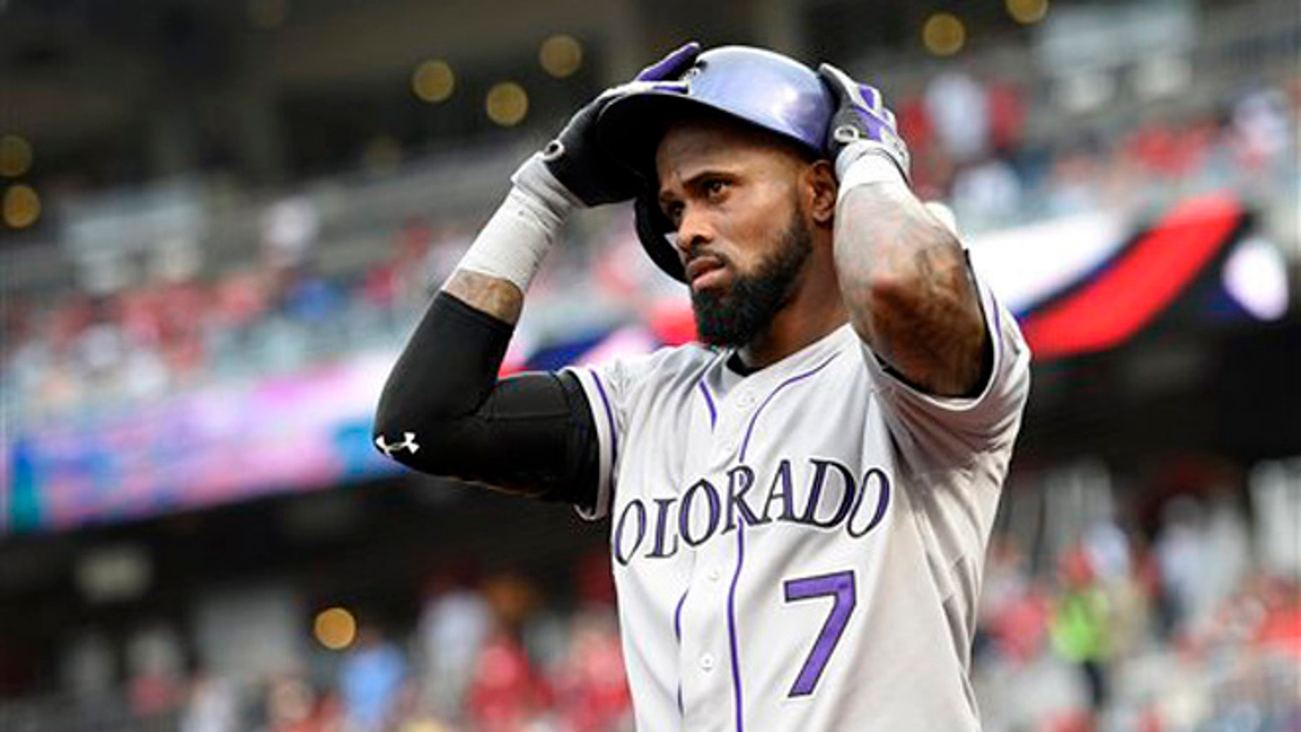 In this Aug. 7, 2015, file photo, Colorado Rockies shortstop Jose Reye adjusts his batting helmet before a baseball game against the Washington Nationals in Washington.
