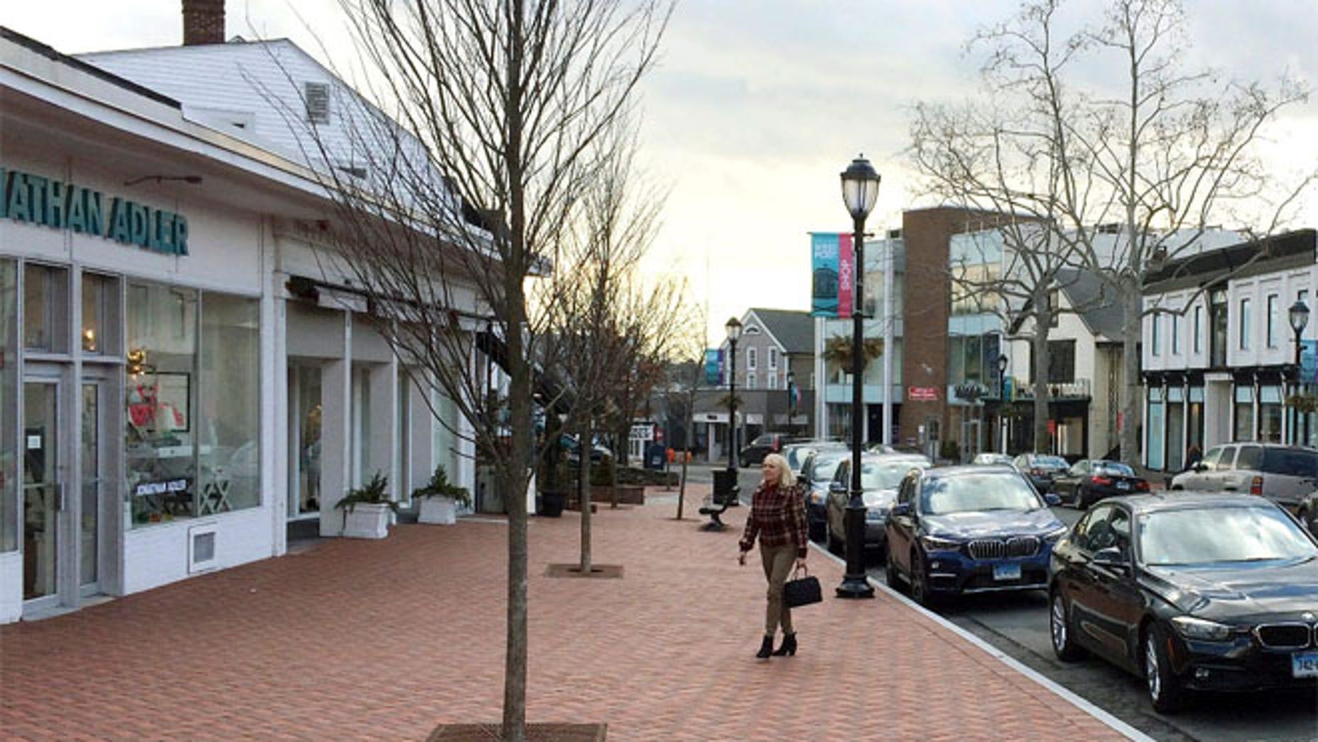 Jan. 26, 2017 photo, a woman walks near shops in downtown Westport, Conn.