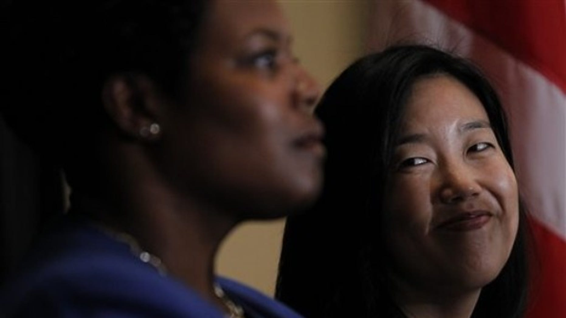 DC Schools Chancellor Michelle Rhee, right, smiles during an announcement that she is resigning, Wednesday, Oct. 13, 2010, during a news conference in Washington. (AP)
