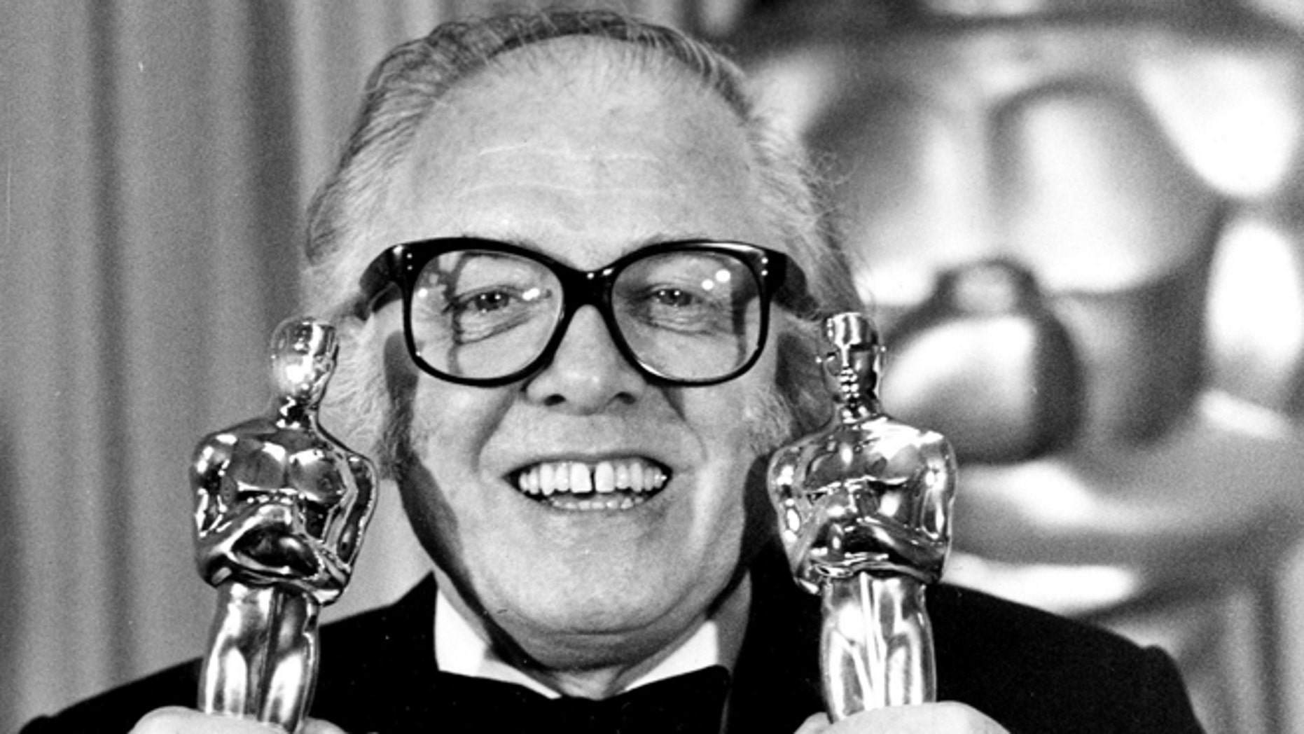 """In this Monday, April 11, 1983 file photo, British actor and director Richard Attenborough holds his two Oscars for his epic movie """"Gandhi"""" at the 55th annual Academy Awards in Los Angeles, Ca. Acclaimed actor and Oscar-winning director Richard Attenborough, whose film career on both sides of the camera spanned 60 years, died on Sunday, Aug. 24, 2014. He was 90."""