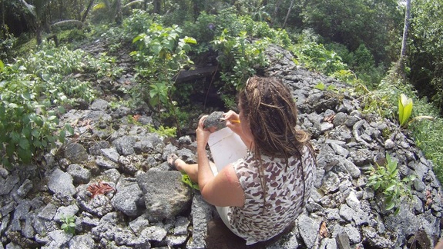 Researcher Zoe Richards inspects the corals used to build a royal tomb at Leluh known as Bat.